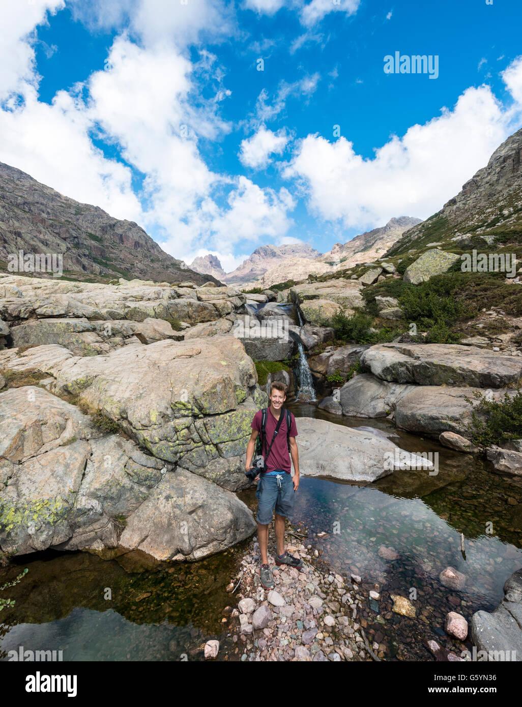 Giovane uomo in piedi in una piscina con una piccola cascata in montagna, fiume Golo, Parco Naturale della Corsica Immagini Stock
