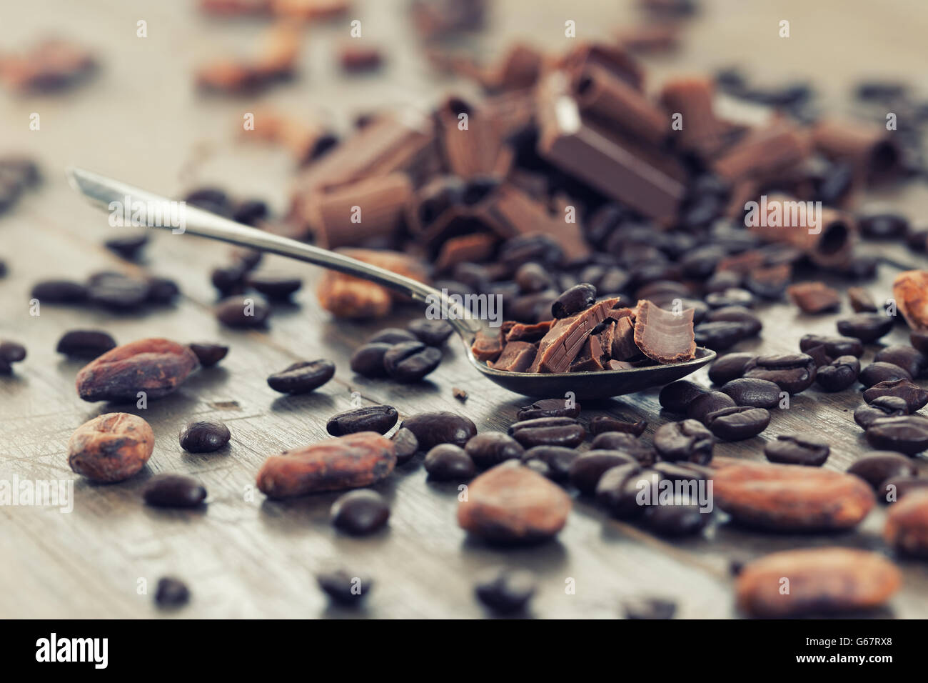 Pezzetti di cioccolato con cacao e caffè in grani su una tavola di legno Immagini Stock