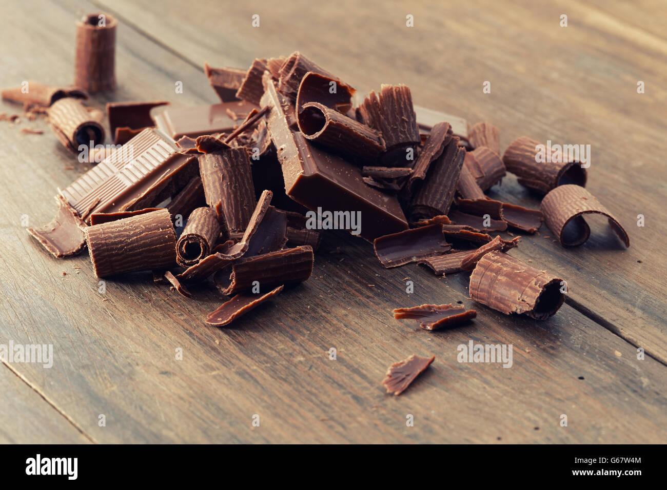 Rotture di cioccolato fondente e scaglie di cioccolato su un tavolo di legno Immagini Stock