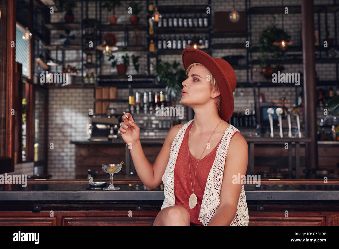 Ritratto di attraente giovane donna di fumare in un bar. Azienda di sigarette e di guardare lontano. Immagini Stock