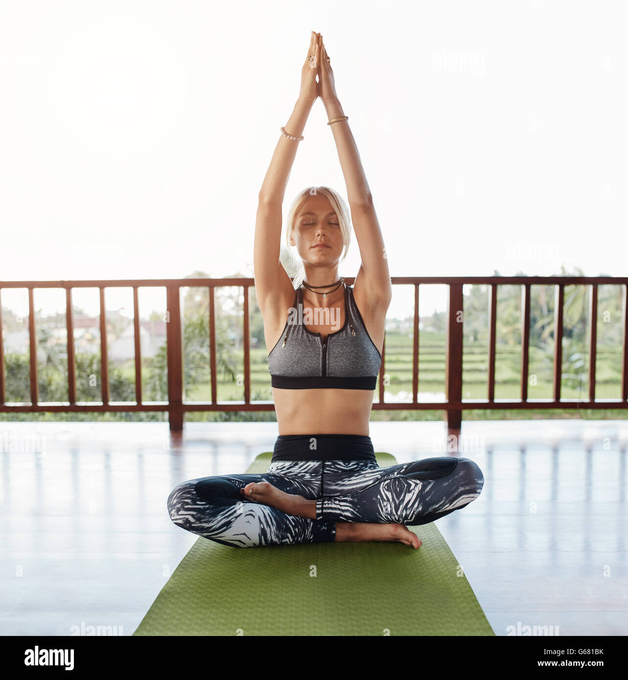 Giovane donna seduta sul pavimento nella posa di yoga con le mani giunte overhead. Fitness modello femmina facendo Immagini Stock
