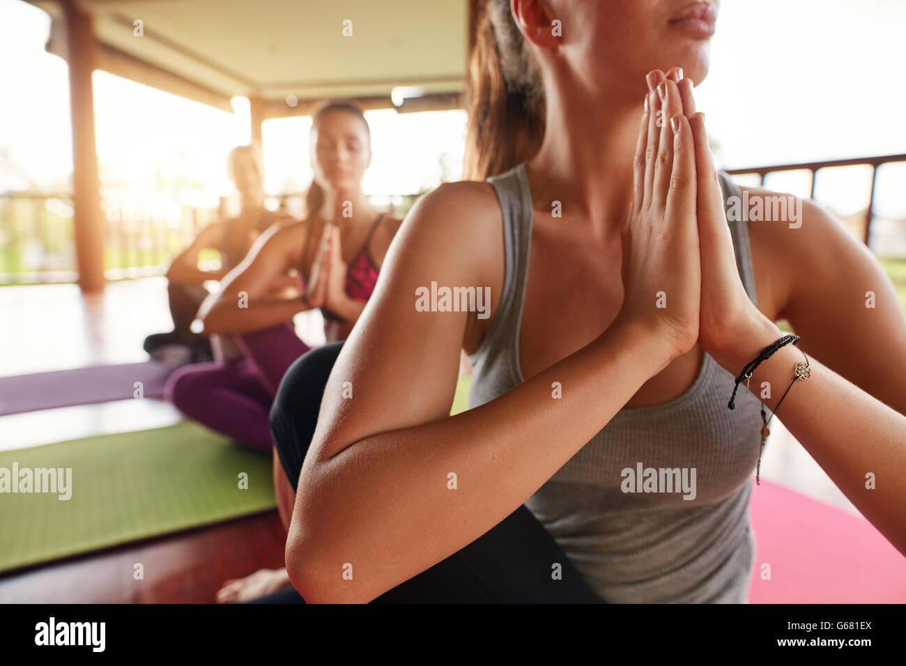 Immagine ravvicinata di giovane donna in classe di yoga a praticare lo yoga. Persone facendo ardha matsyendrasana Immagini Stock