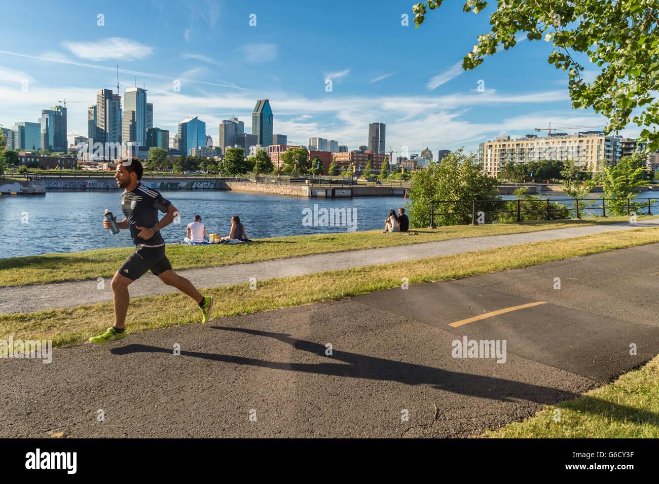 Lachine Canal il percorso in Montreal, con skyline in background e un giovane uomo che corre Immagini Stock