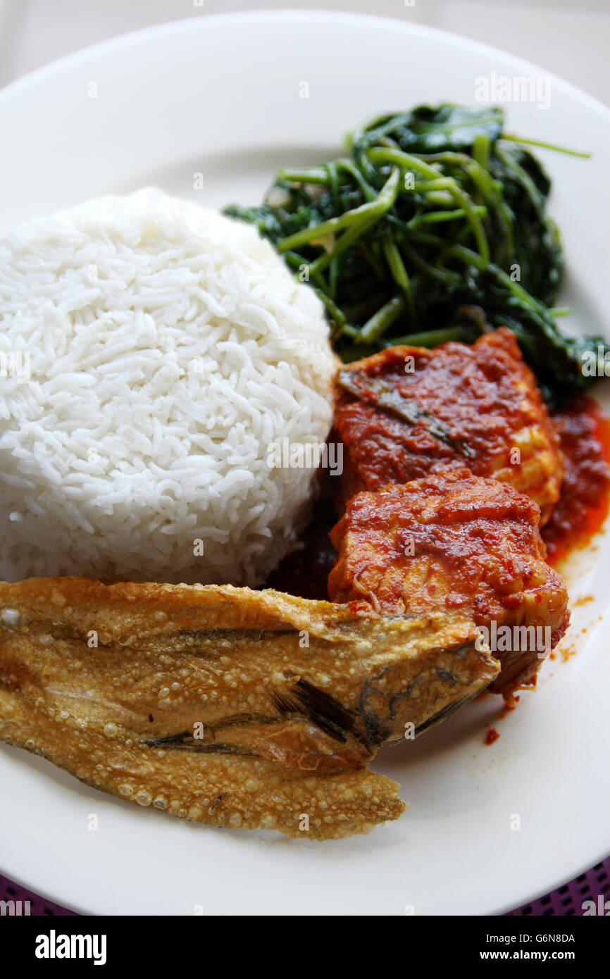 Close up di riso bianco e piccante piatto di pesce con patatine fritte spinaci acqua - Asam pedas ikan pari Immagini Stock