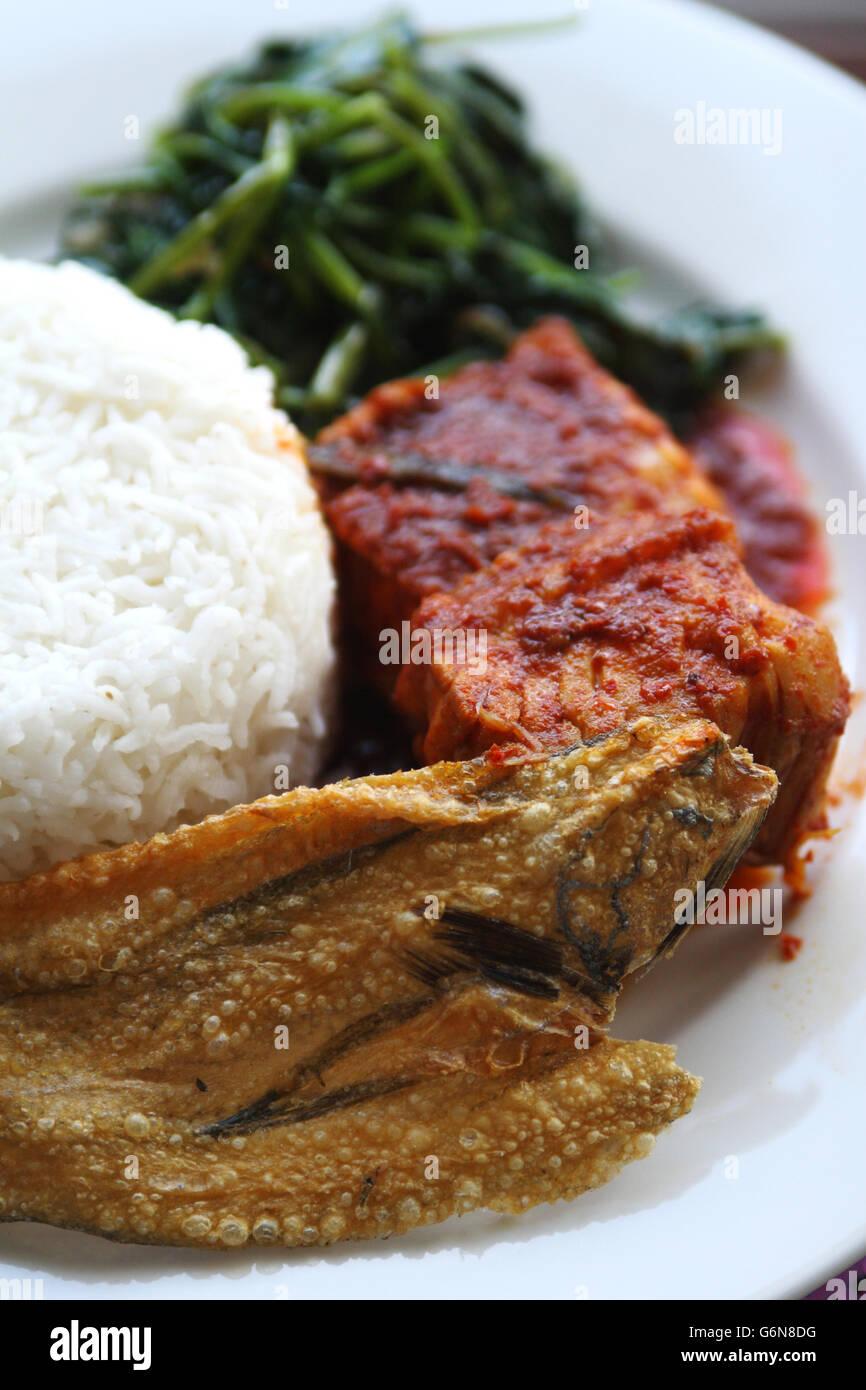 Close up di riso bianco e piccante piatto di pesce con patatine fritte spinaci acqua e pesce salato servita su piastra Foto Stock