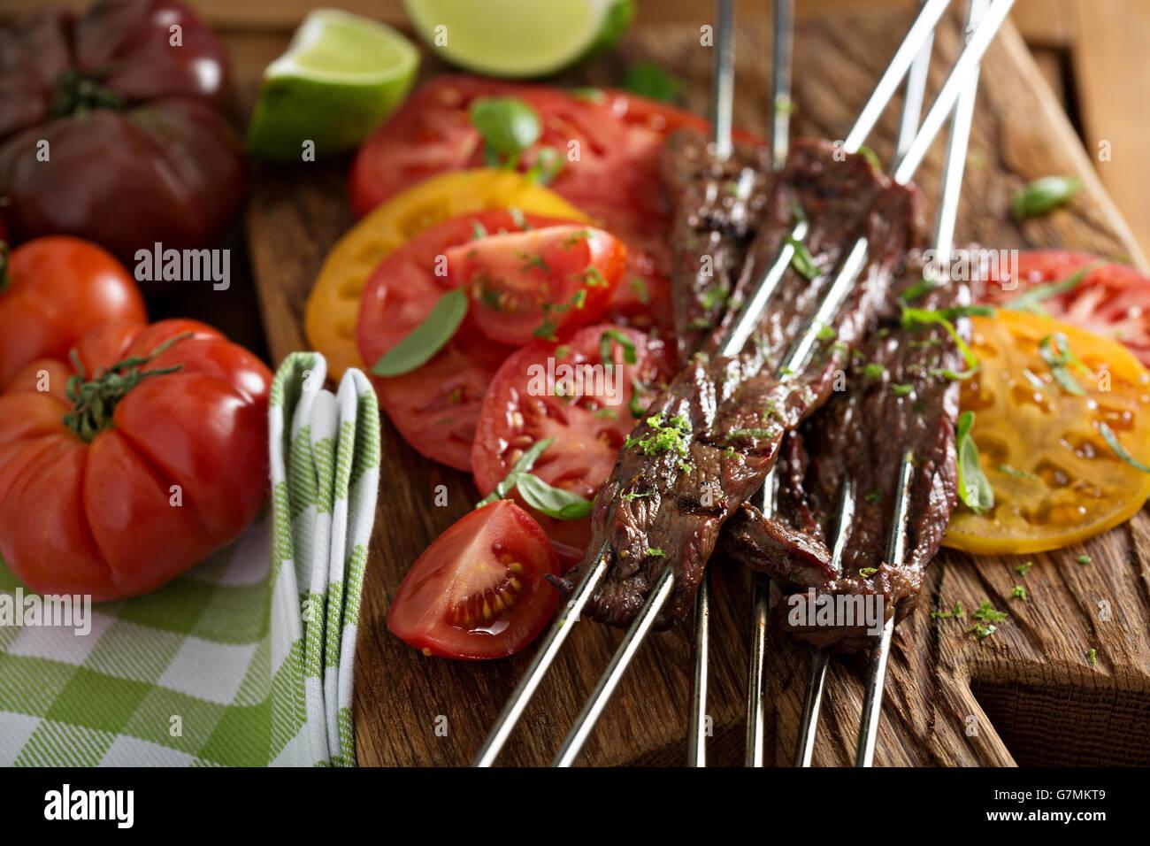 Bistecca di fianco su spiedini con pomodori Immagini Stock