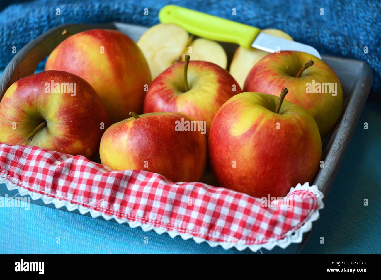 Close up di rosso, giallo ,Mele Verdi nella ciotola di legno con coltello e fette di mela rossa nostalgico bianco Immagini Stock