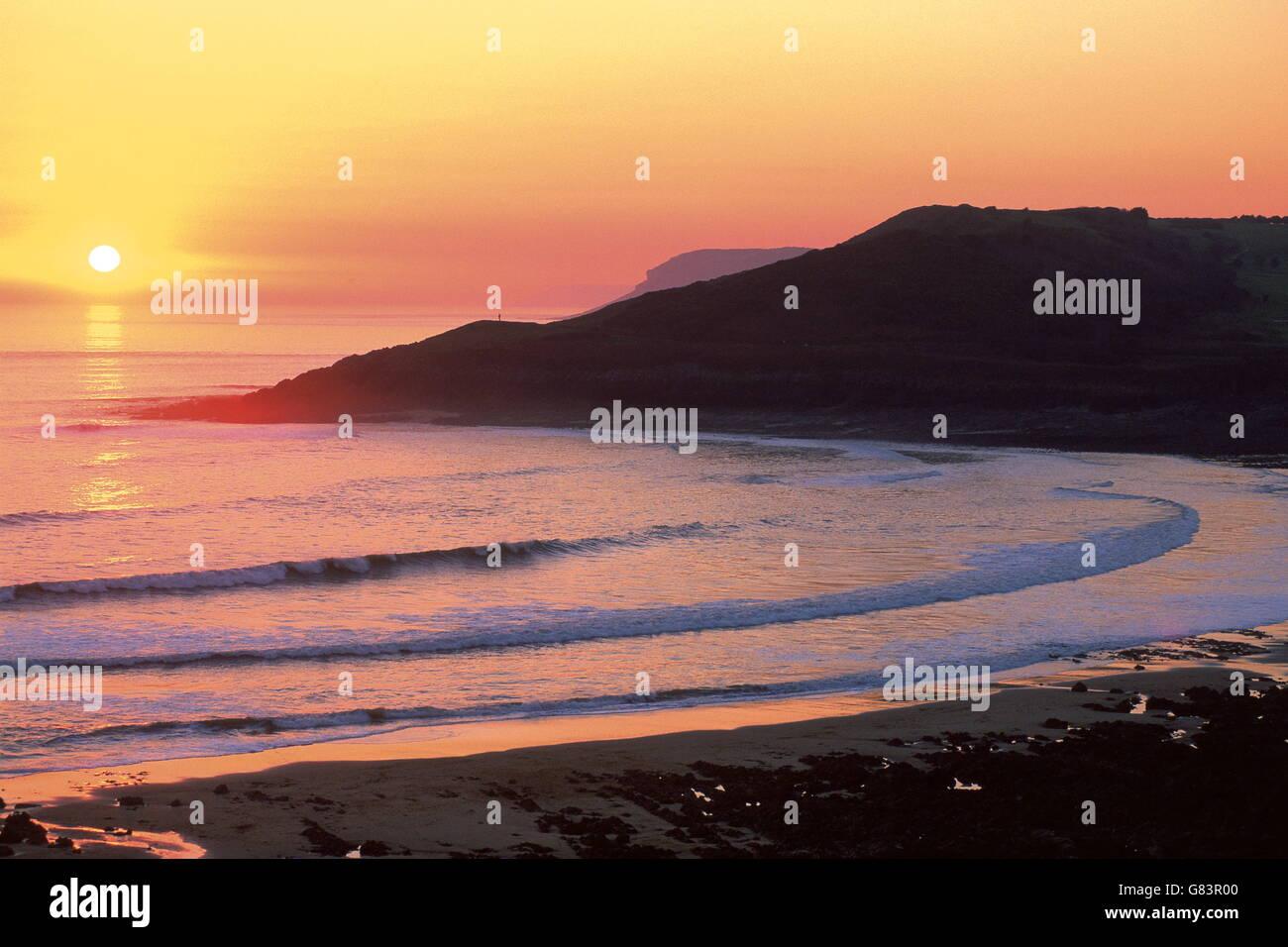 Classic arancione tramonto sulla spiaggia .curva onde nella baia sotto al riparo da promontori. Immagini Stock