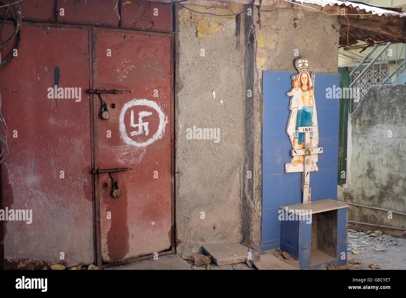 Una svastica o segno swastik dipinta su una porta, accanto a un cattolico di Maria e Gesù santuario a Bandra, Immagini Stock