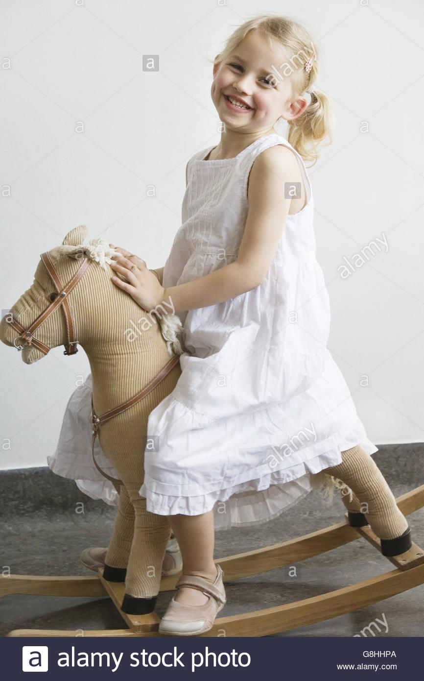 Scuola materna ragazza seduta sul cavallo a dondolo Immagini Stock