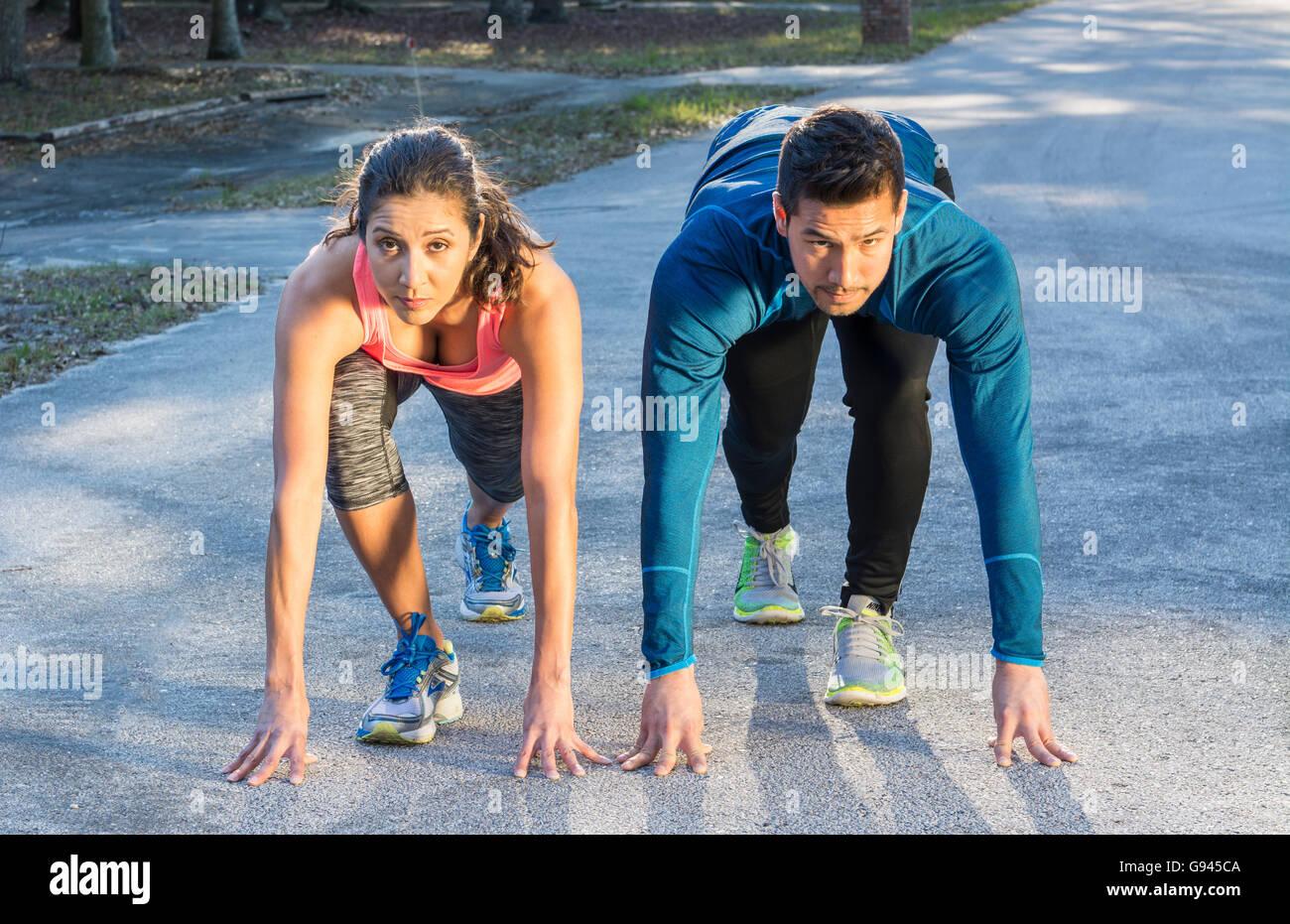 I giovani ispanici coppia spagnola in esecuzione della concorrenza sulla linea di partenza tesa concorso vincente Immagini Stock