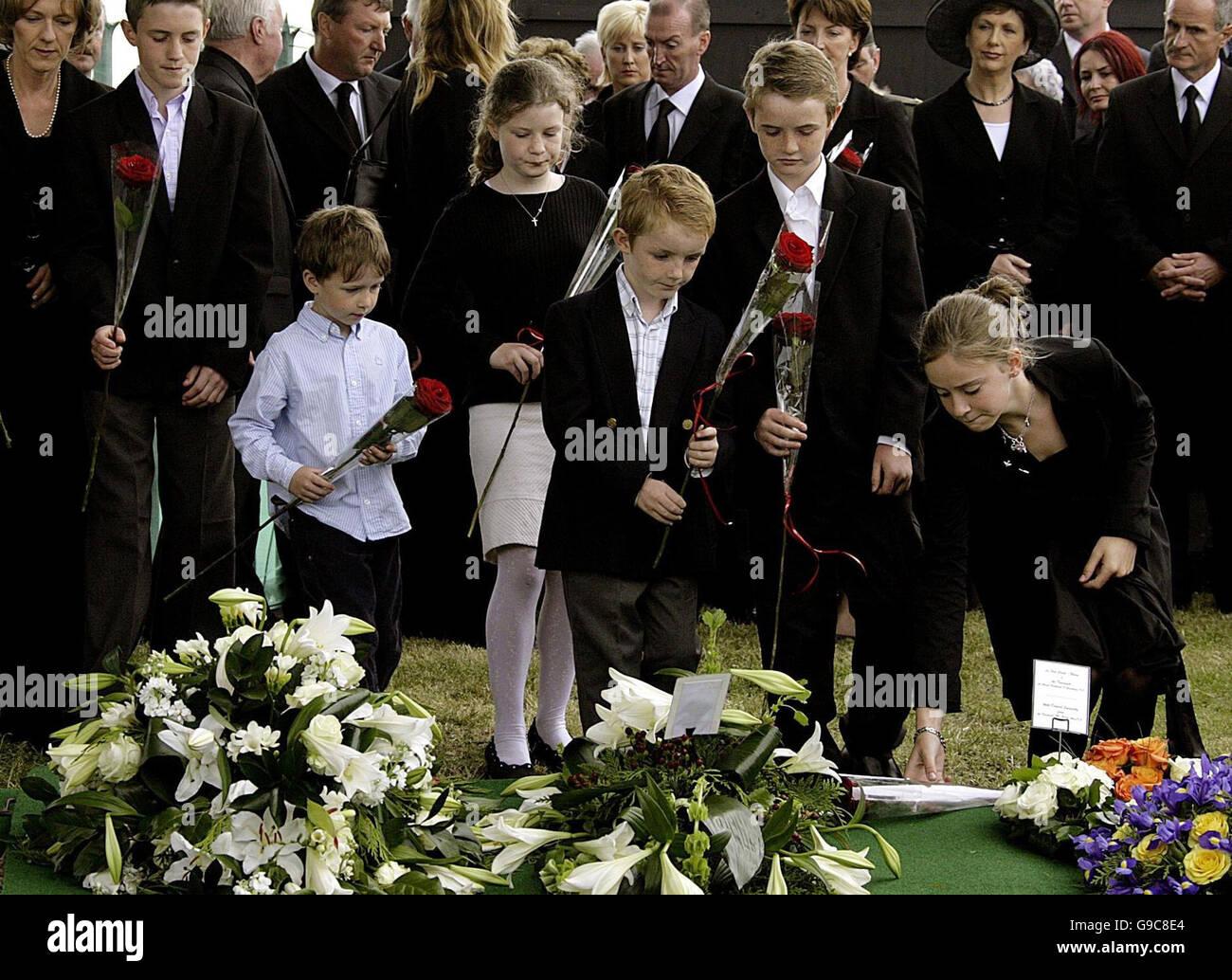 Haughey's grand-bambini porre fiori all'graveside dell ex Primo Ministro Charles Haughey durante il servizio Immagini Stock