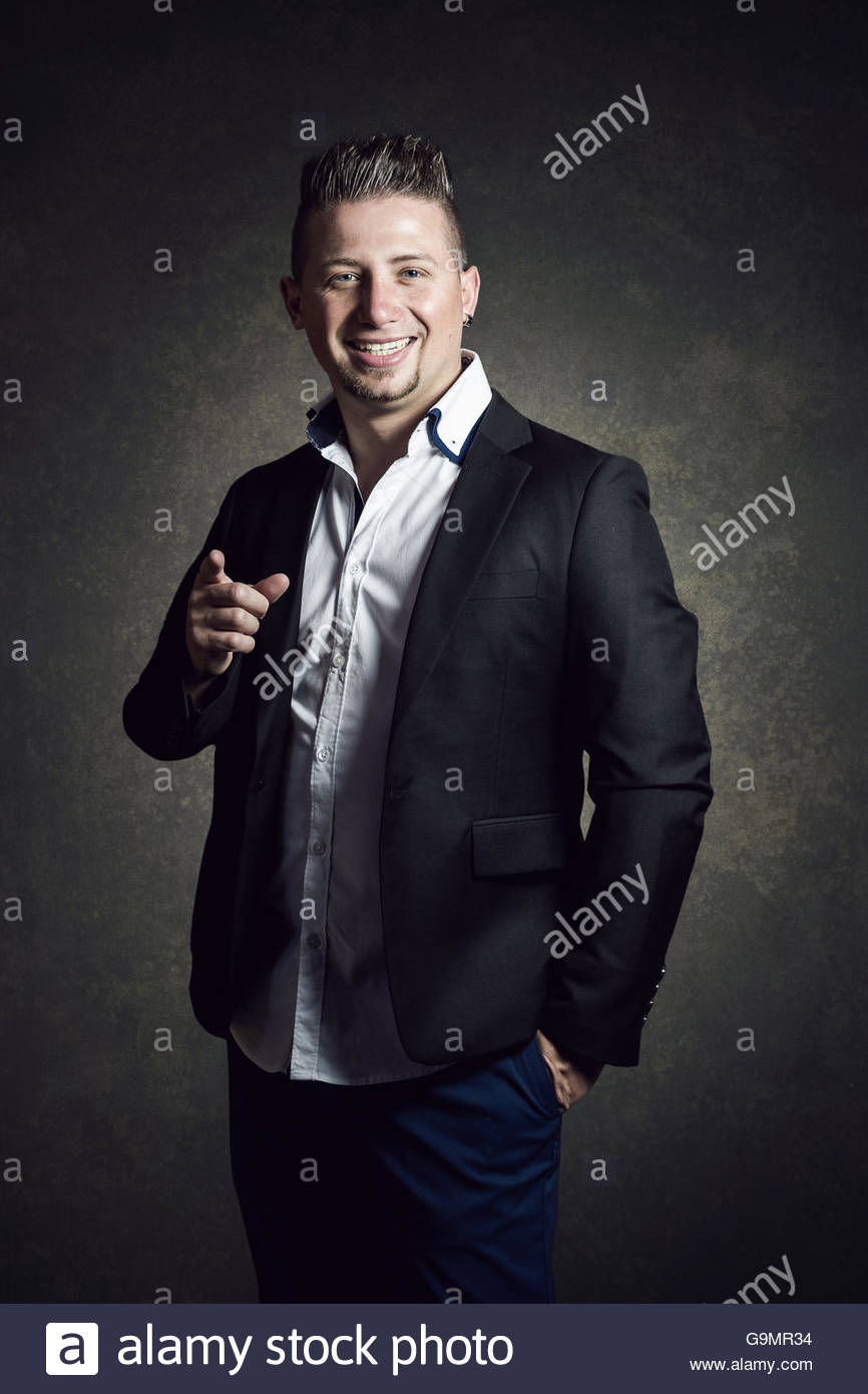 Elegante imprenditore sorridente con la camicia puntando con il dito Immagini Stock