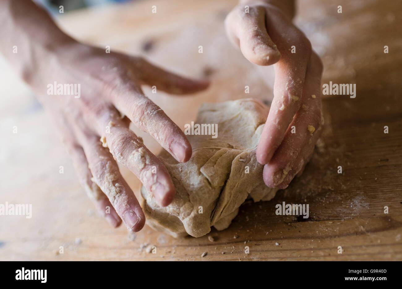 Close-up di due forti mani di un fornaio che sono manualmente gli impasti su una ruvida, cucina in legno tabella Immagini Stock