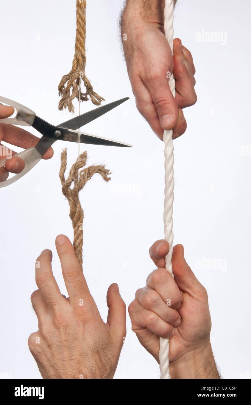 Mano trattiene una fune, Forbici taglia la stessa stringa Immagini Stock