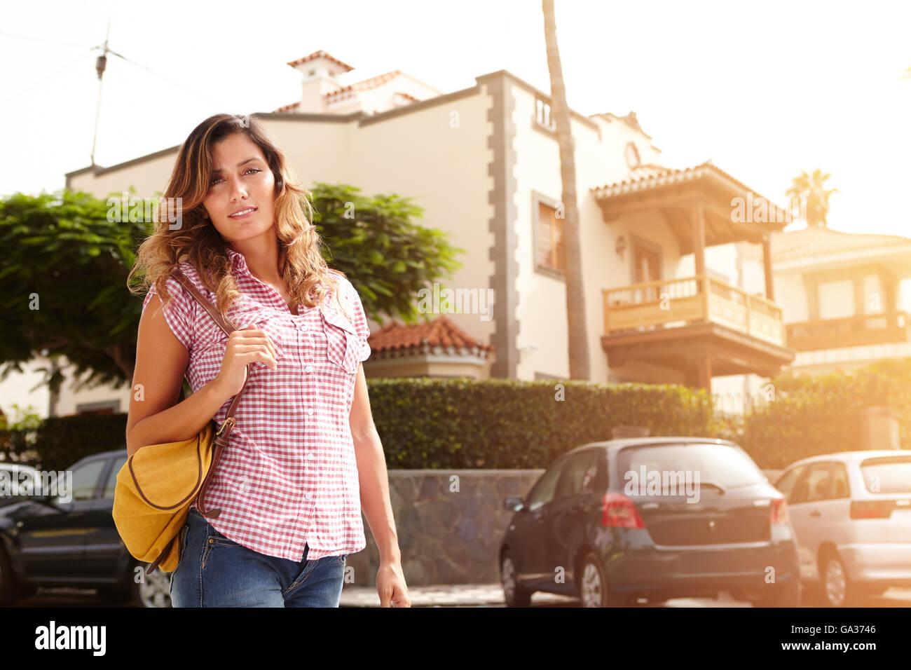 La donna caucasica con medio-lunghezza capelli camminare per la strada al tramonto Immagini Stock