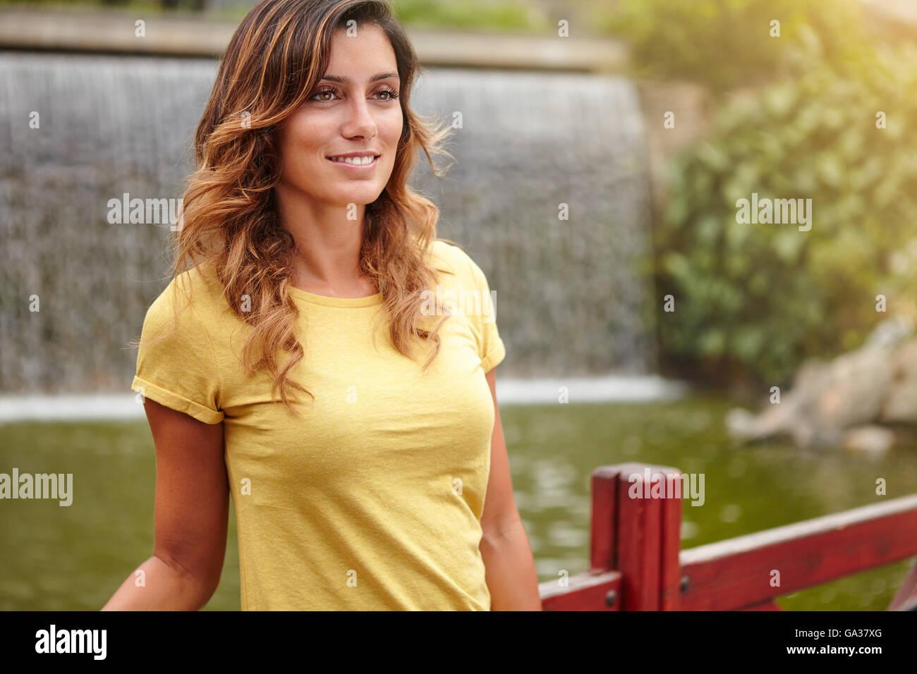 Signora giovane con medio-lunghezza capelli sorridere mentre in piedi vicino parco lago Immagini Stock