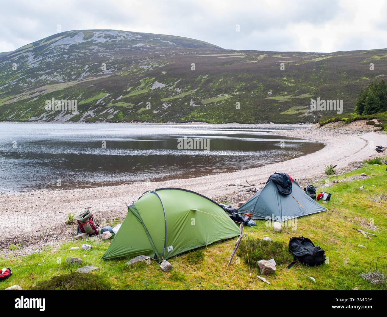 Due tende su un Loch shore in Cairngorm montagne in Scozia Immagini Stock