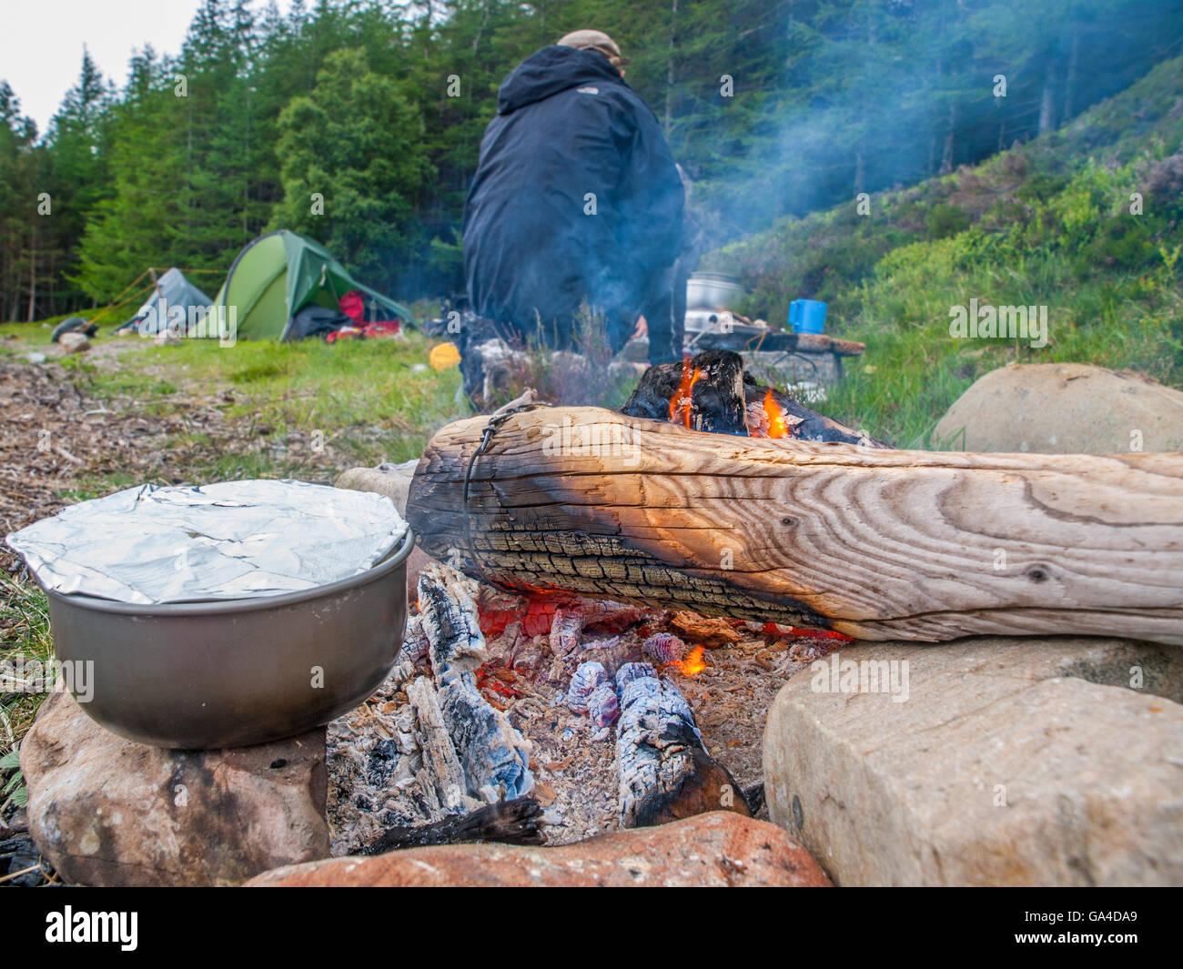Un recipiente di cottura su un fuoco di campo, camper e tende in background. Highlands scozzesi Immagini Stock