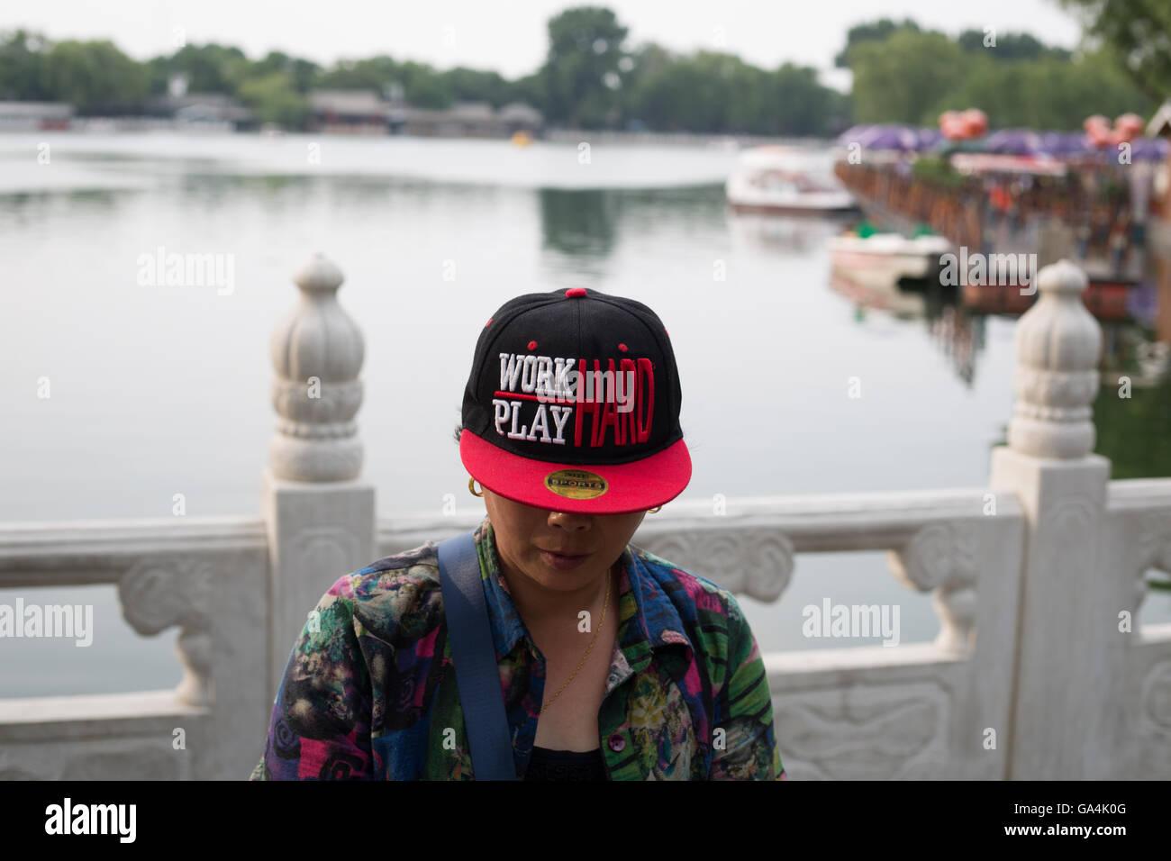 Donna che indossa hat leggere 'lavorare duro, il gioco si fa duro', a Bei Hai e Hou Hai area lacustre di Immagini Stock