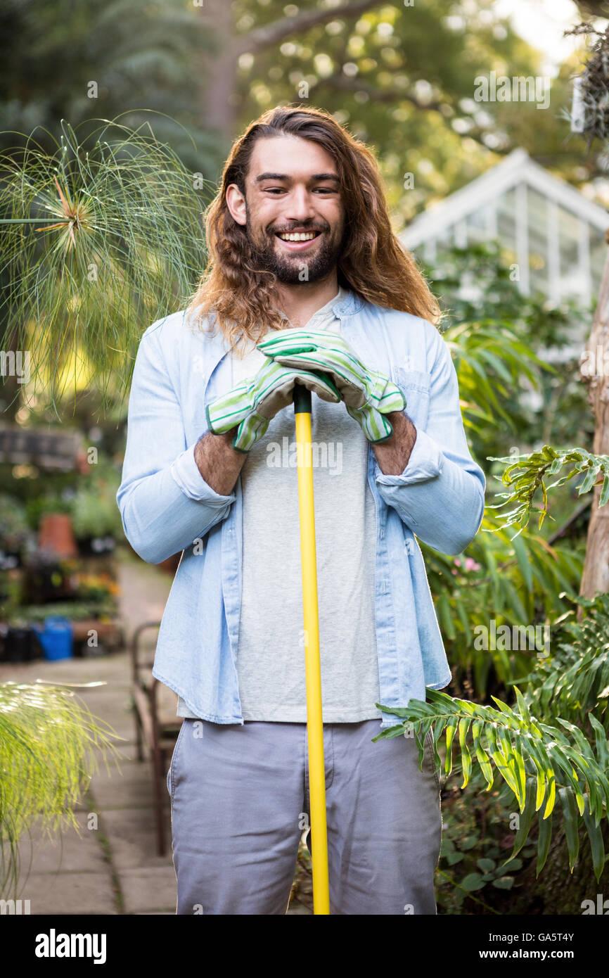 Ritratto di felice giardiniere con capelli lunghi tenendo l'attrezzo in giardino Immagini Stock