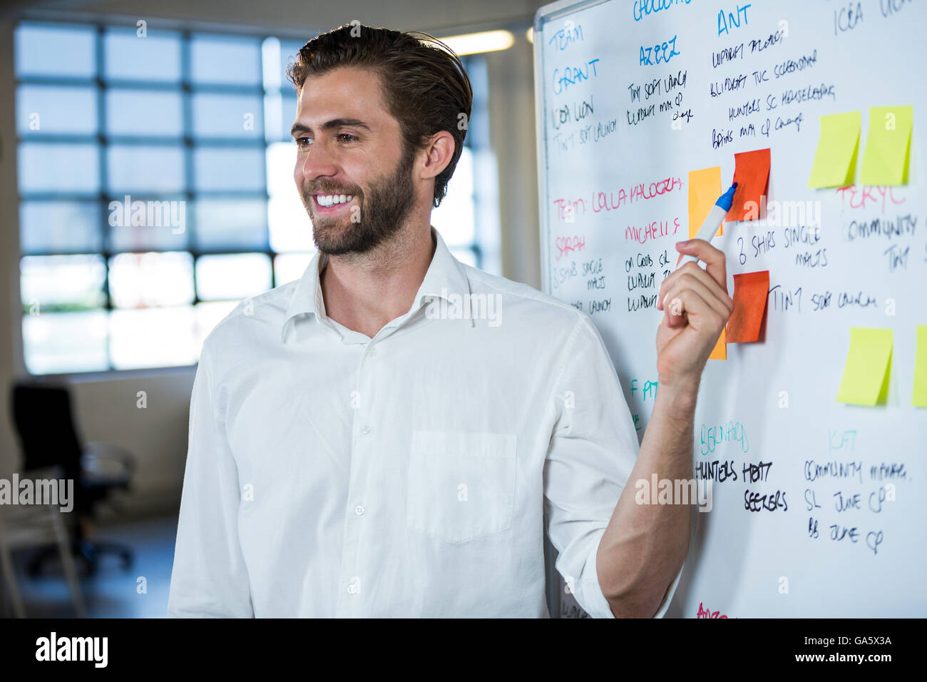 Imprenditore sorridente puntando su una nota adesiva Immagini Stock
