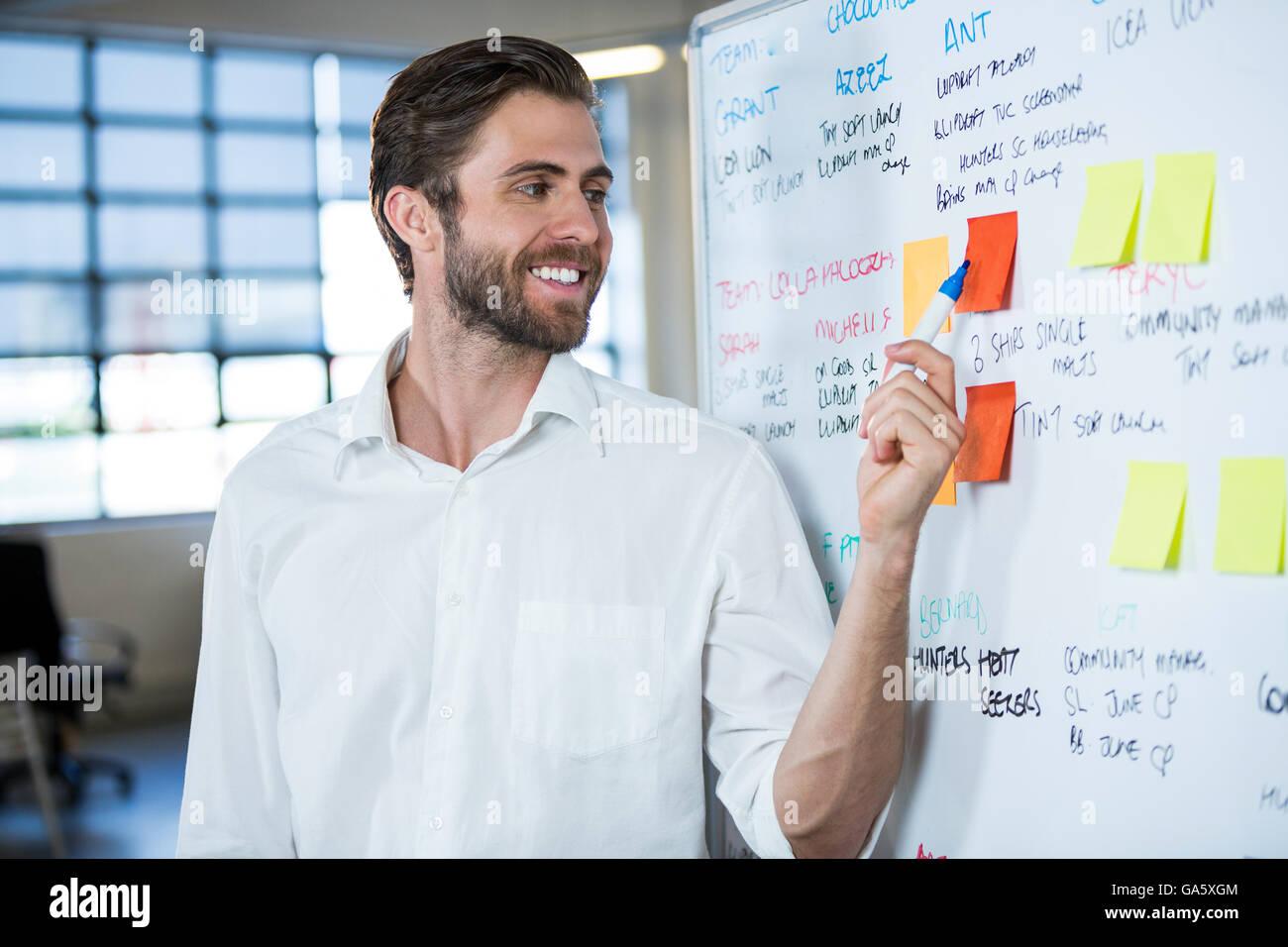 Imprenditore sorridere mentre puntando su una nota adesiva Immagini Stock