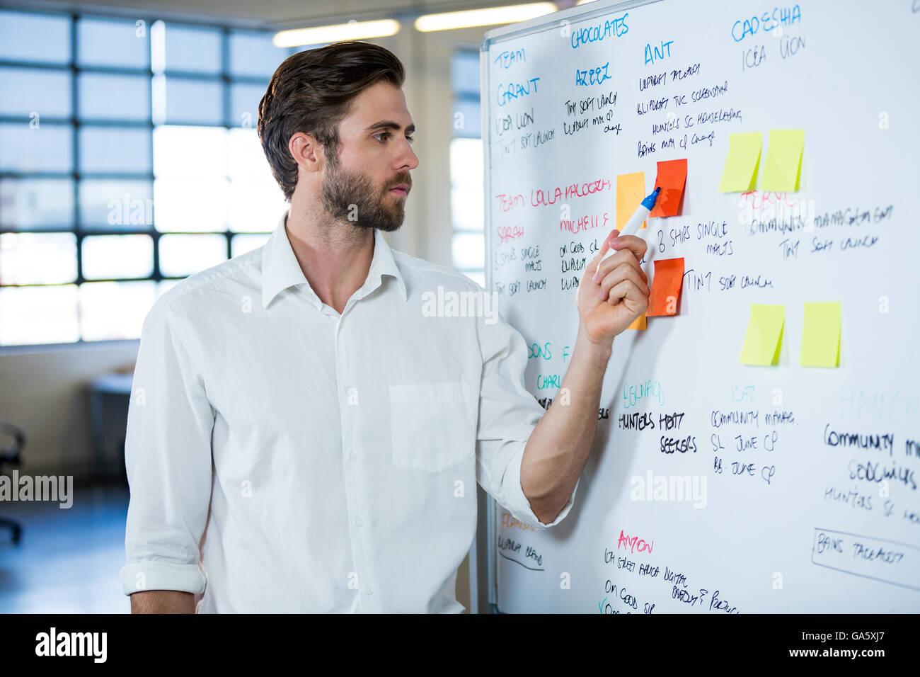 Imprenditore puntando su una nota adesiva Immagini Stock