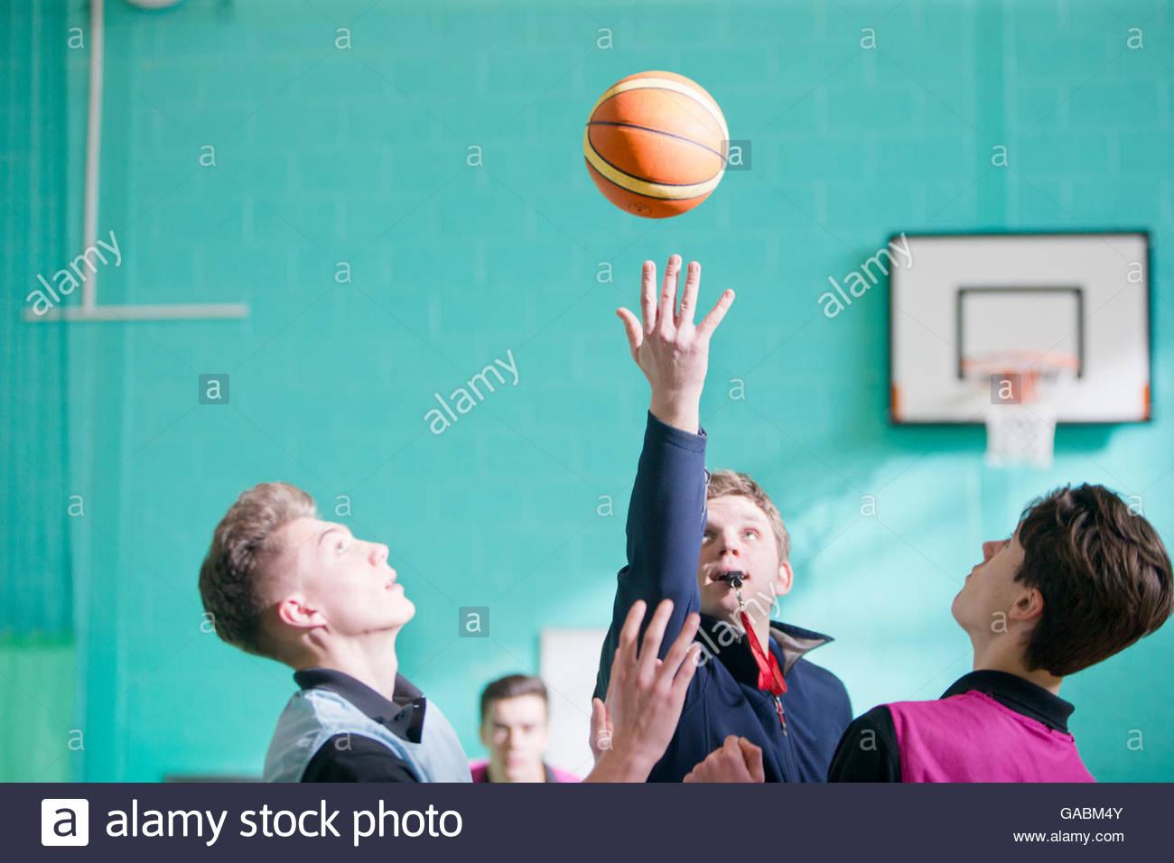 Palestra insegnante a partire high school gioco di basket con tip off Immagini Stock