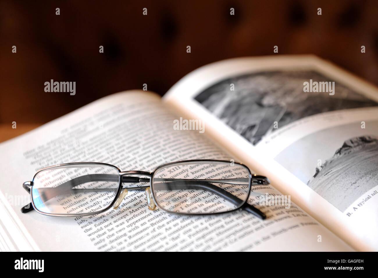 Gli occhiali da lettura sulla parte superiore del libro di antichità Immagini Stock