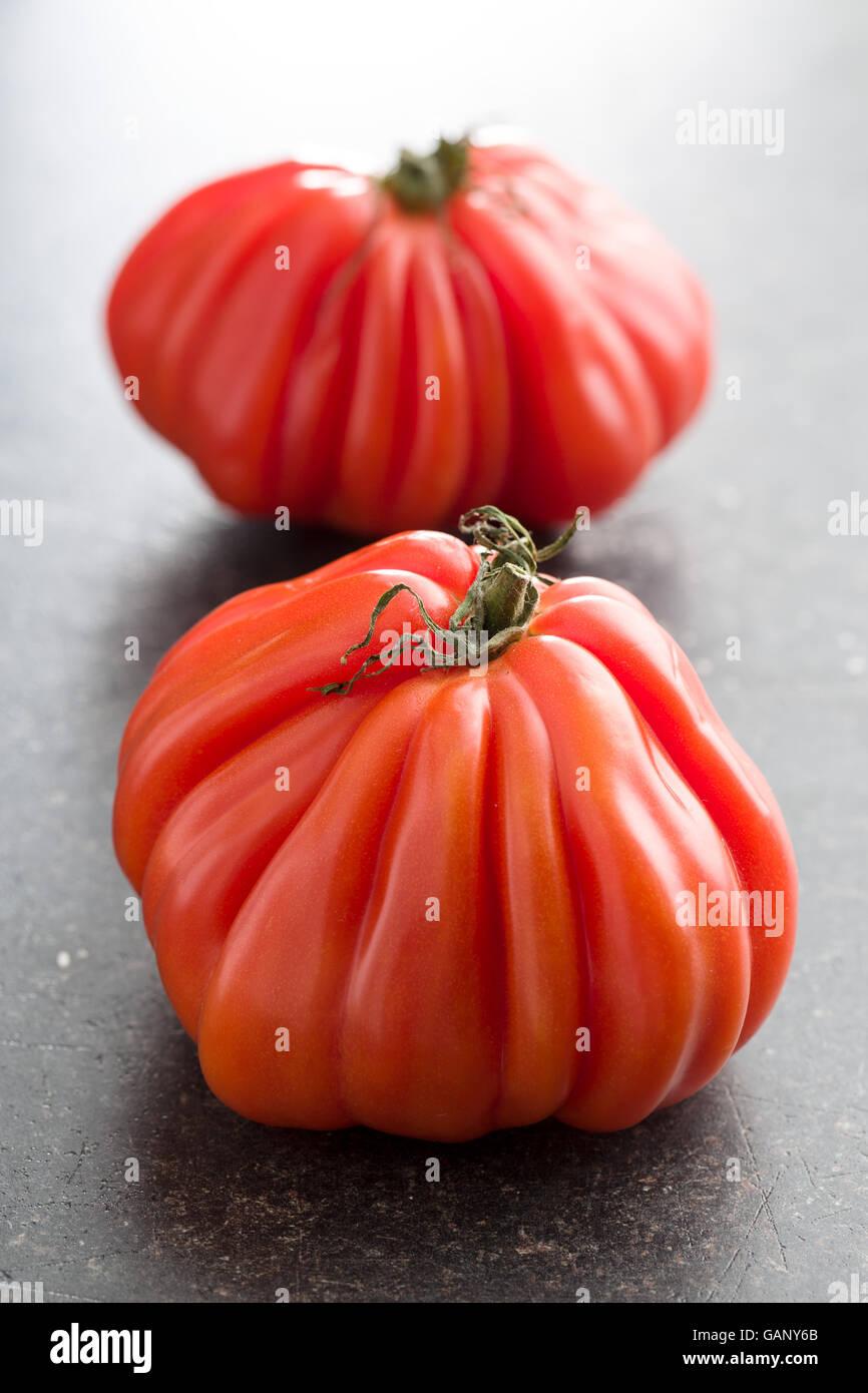 Coeur de boeuf. Bistecca di manzo pomodori sul vecchio tavolo da cucina. Immagini Stock
