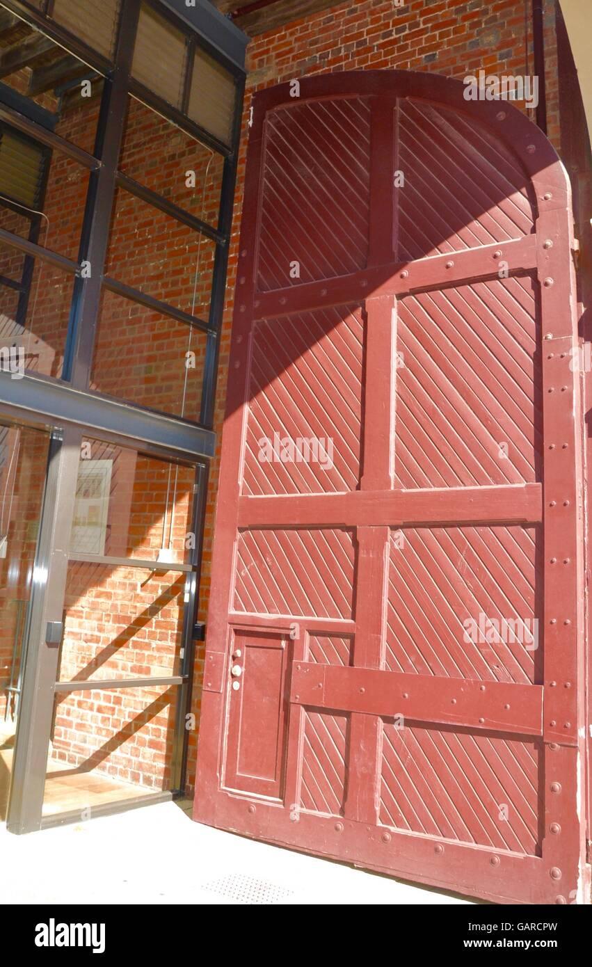 Gigante rosso mattone colorato porta in legno un accento particolare su un edificio in mattoni esterno con una parete Immagini Stock