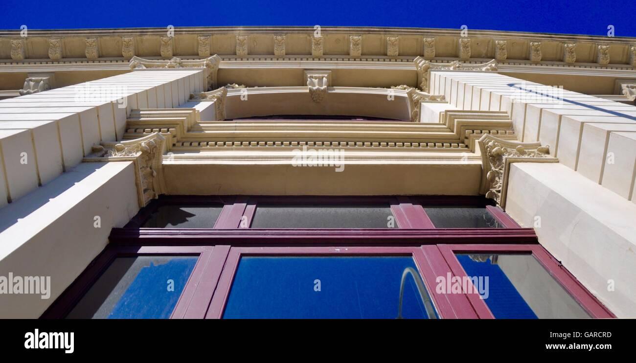 Prospettiva verso l'alto del vetro architettonico e viola il framing dettagli su esterno dell'edificio ornato Immagini Stock