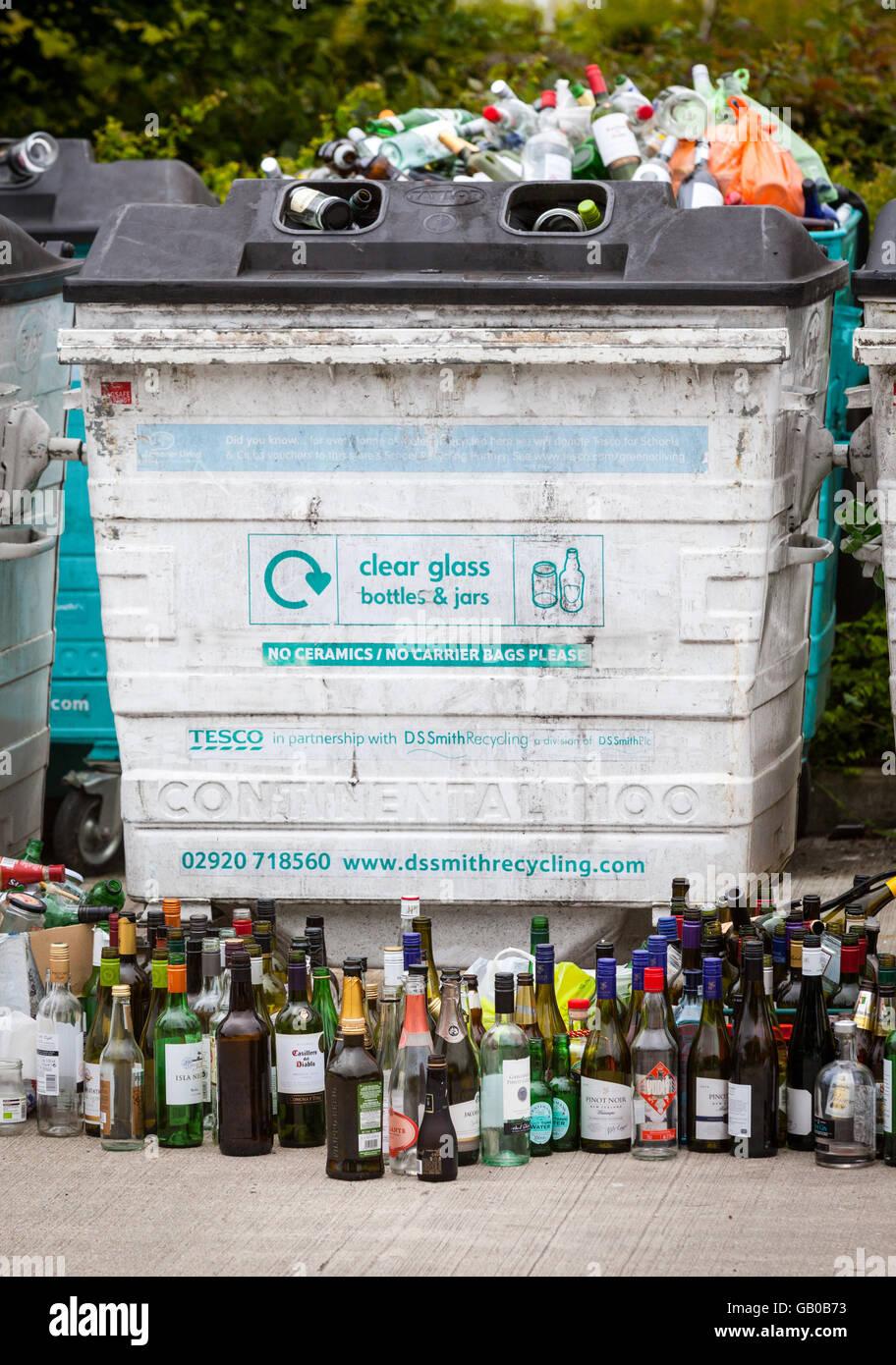 Traboccante di vetro riciclaggio bottle bank in Winchester, Regno Unito con file di bottiglie di vino allineate Immagini Stock