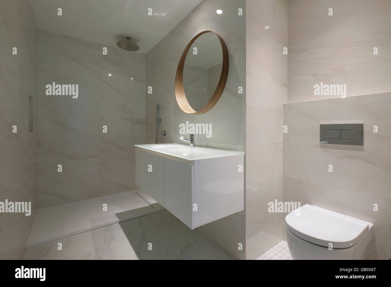 Bagno moderno con pareti in marmo e un grande specchio rotondo