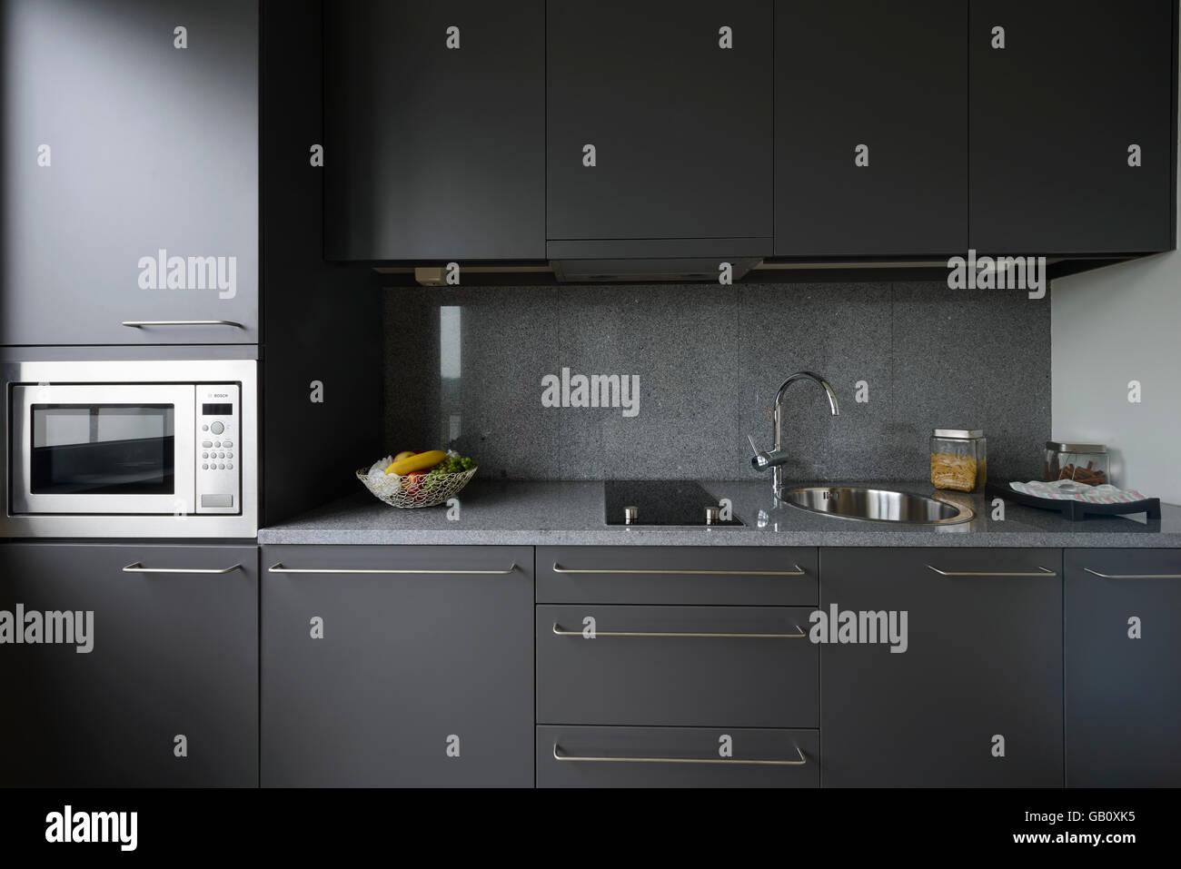 Piccolo e moderno di colore grigio contatore di cucina con forno a ...