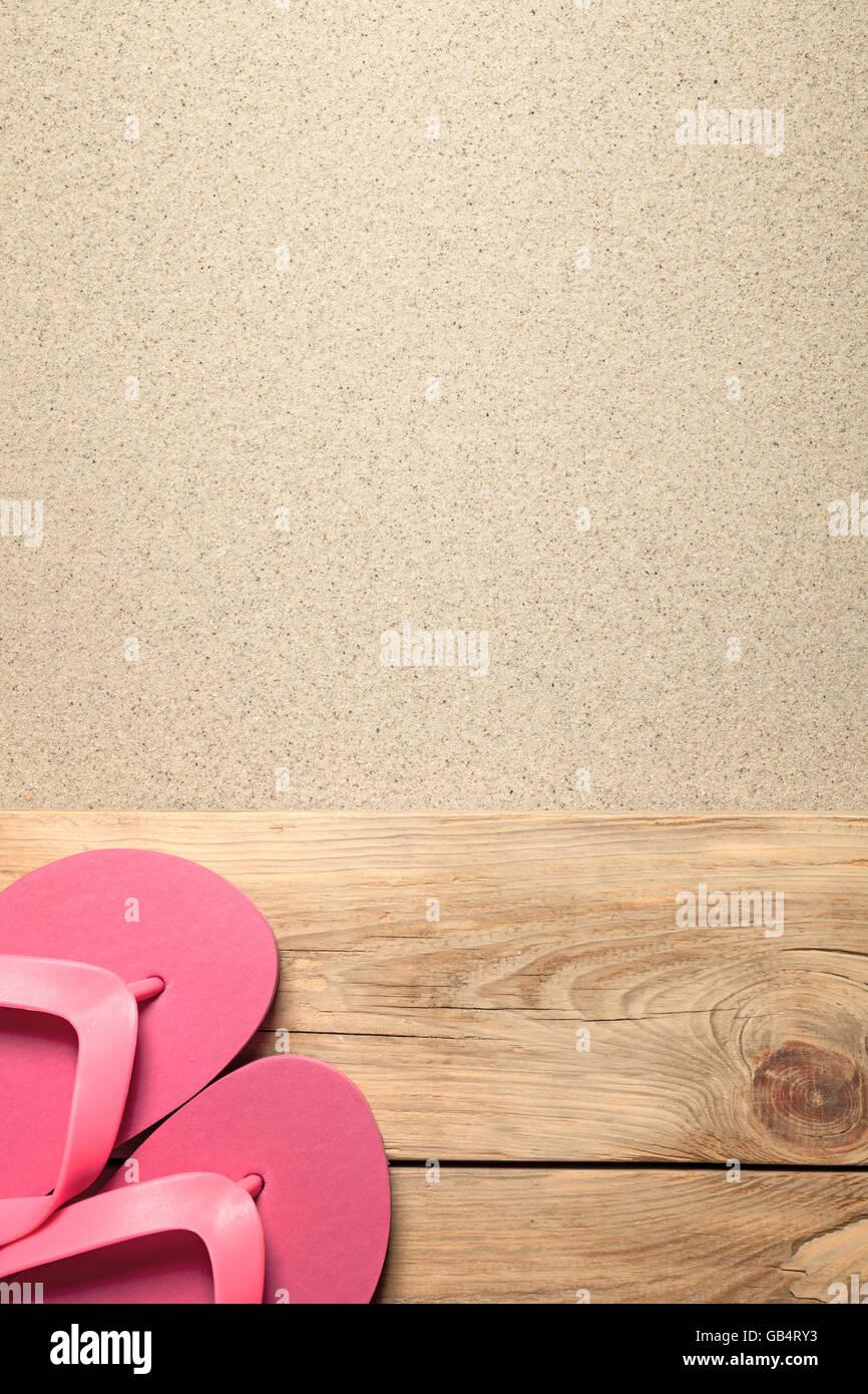Estate con sfondo rosa flip flop sulla spiaggia sabbiosa Foto Stock