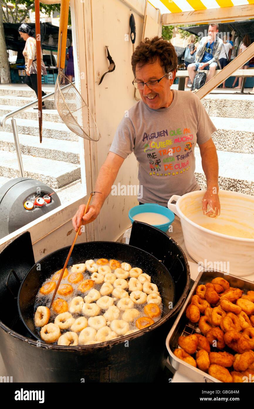 Stallo del mercato trader rendendo ciambelle, Pollensa ( Pollenca ) mercato, Mallorca ( ) di Maiorca, isole Baleari, Immagini Stock