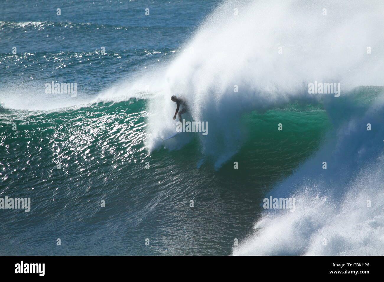 Un maschio di lone surfer scende in su una grande onda durante il big surf a Sandon Point, Bulli, NSW, Australia. Immagini Stock
