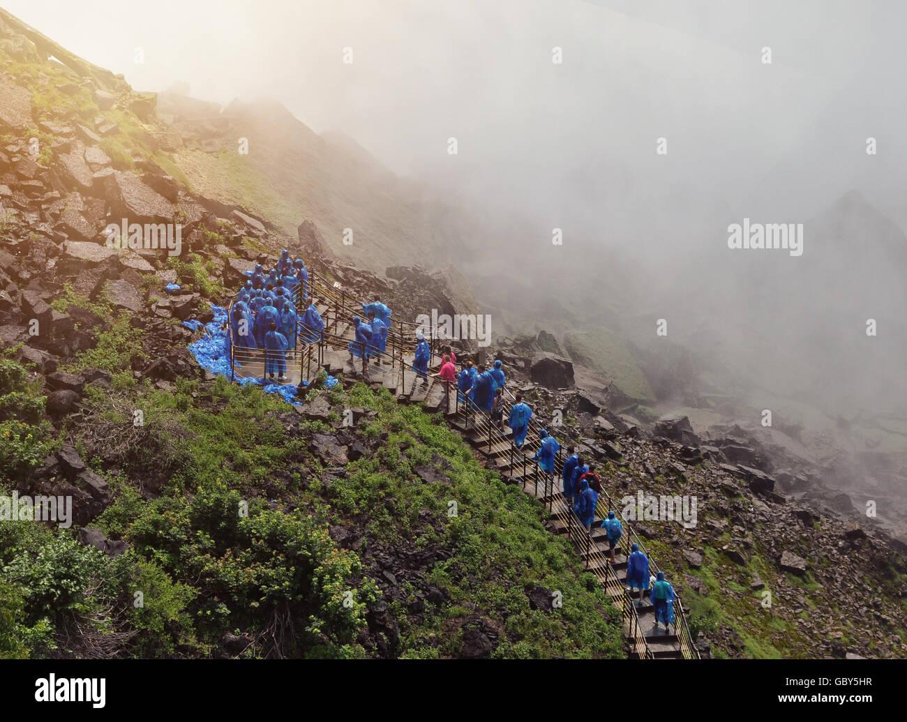 I turisti sono a camminare su una scala per le Cascate del Niagara con wet nebulizzazione di acqua ed impermeabili blu su di un viaggio o di concetto Natura. Foto Stock