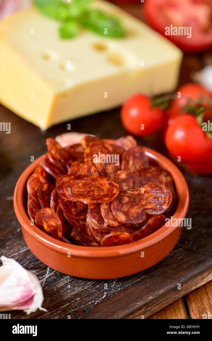 Primo piano di un vaso di terracotta con alcune fette di chorizo spagnolo, un insaccato di maiale tipico della Spagna, Immagini Stock
