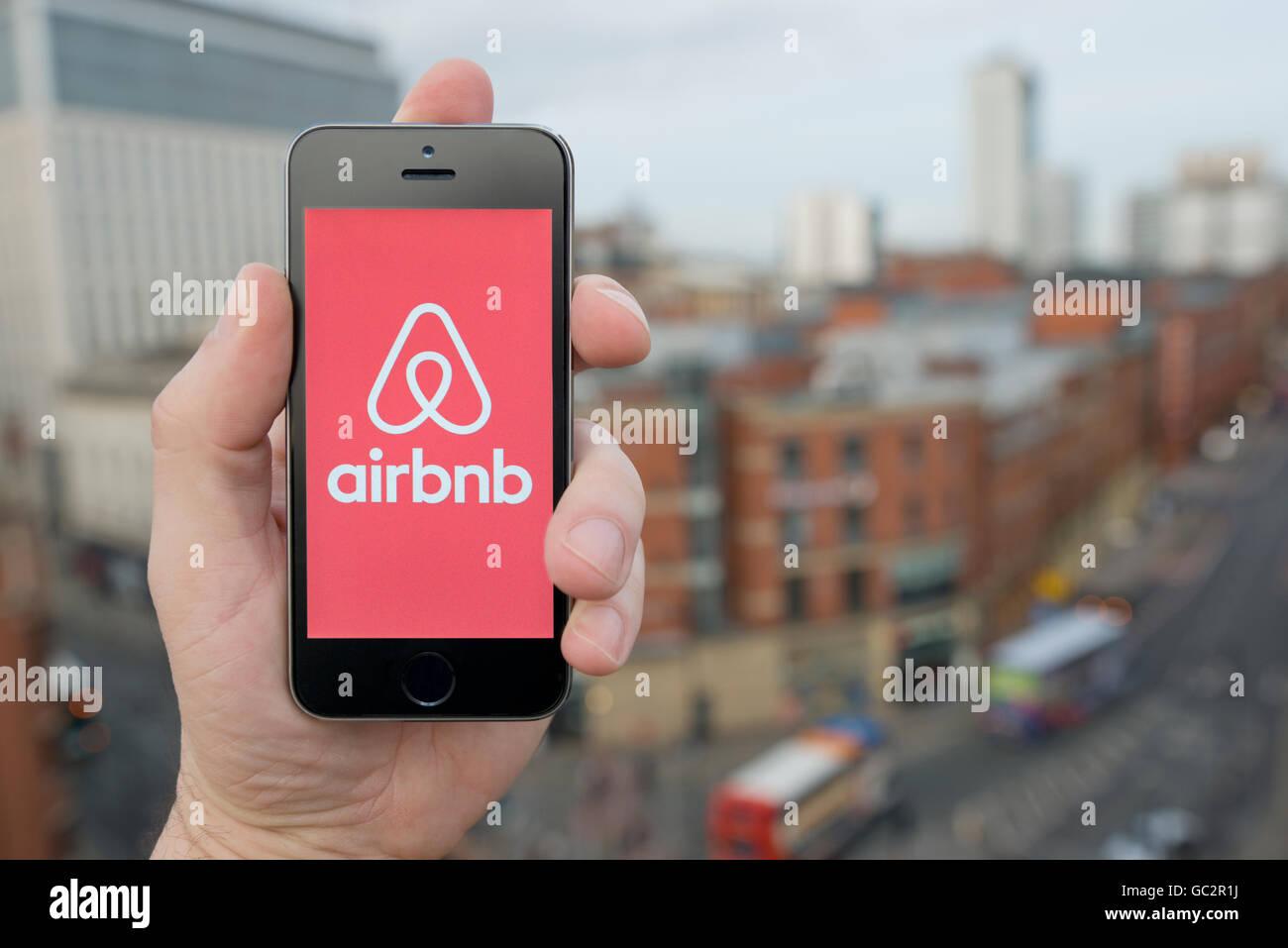 Un uomo utilizza il smartphone Airbnb app mentre si fermò in un alto edificio che si affaccia su una strada Immagini Stock