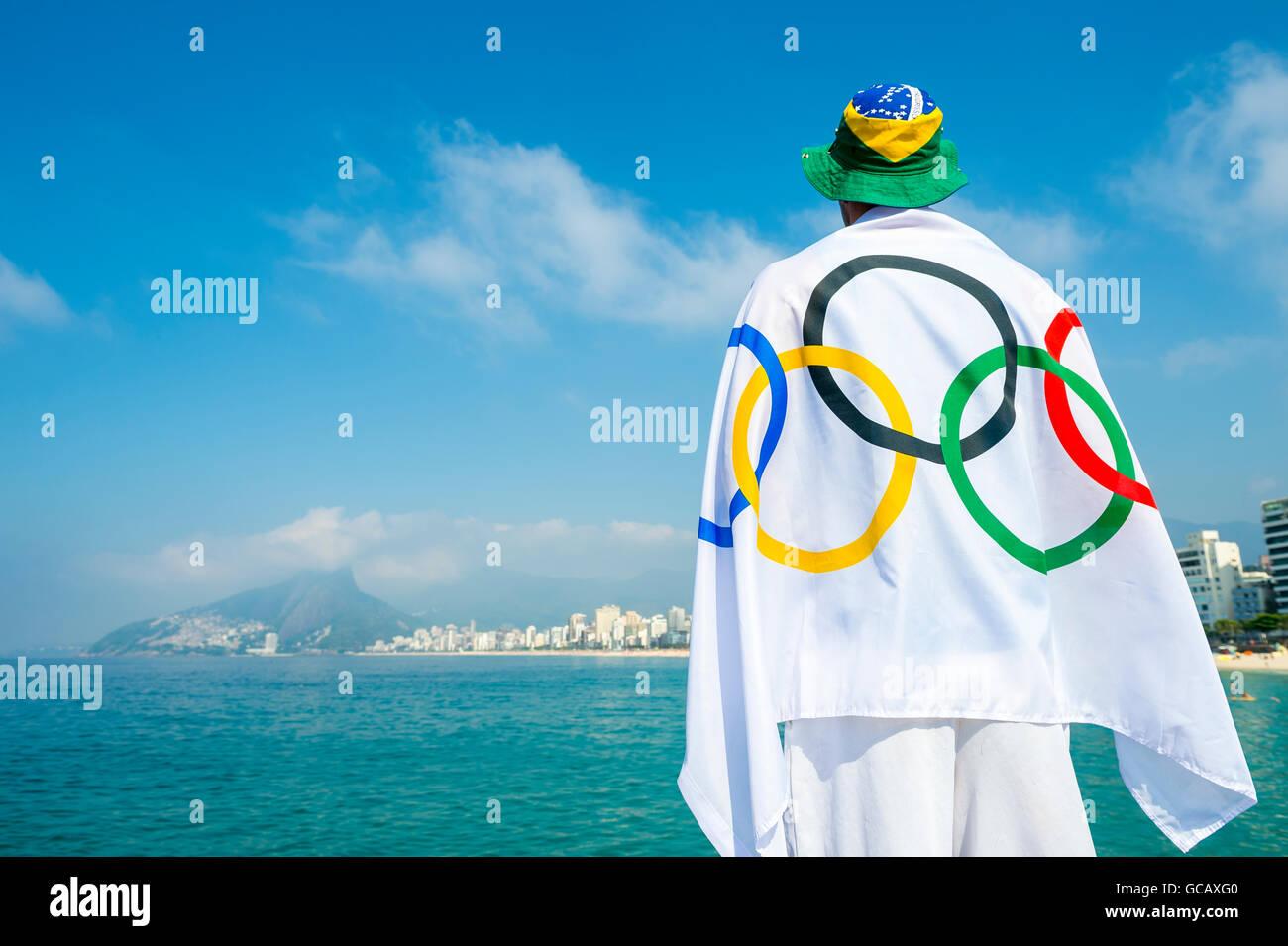 RIO DE JANEIRO - MARZO 27, 2016: atleta drappeggiati in bandiera olimpica sorge sulla spiaggia di Ipanema. Immagini Stock