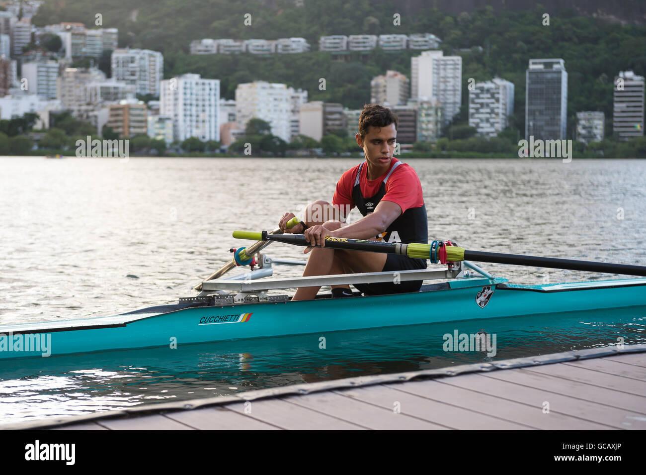 RIO DE JANEIRO - Aprile 1, 2016: un vogatore brasiliano mantiene la sua barca al fianco di un molo a Lagoa Rodrigo Immagini Stock