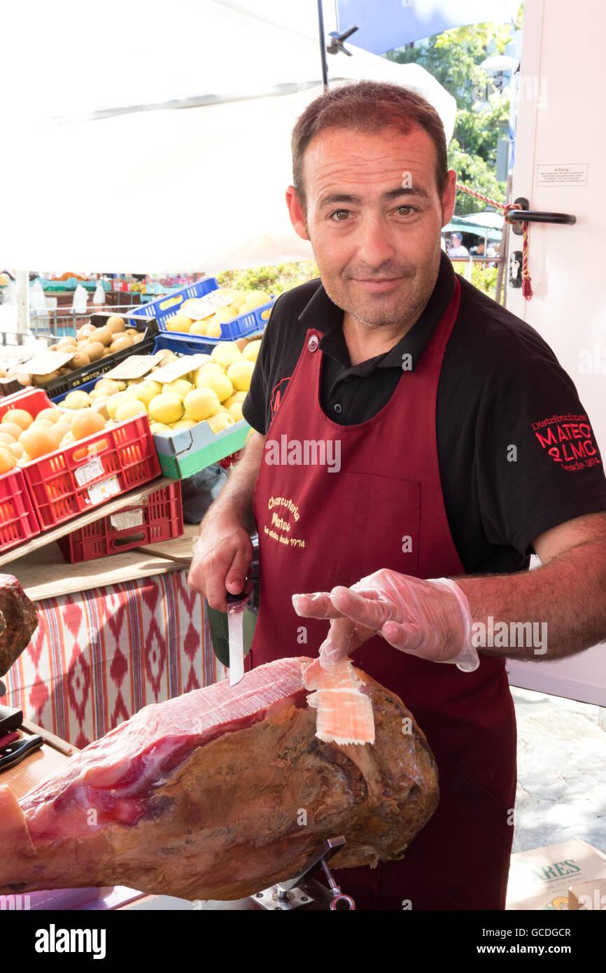 Stallo del mercato trader carving un prosciutto ( Jamon ), Pollensa ( Pollenca ) mercato, Mallorca ( ) di Maiorca, Immagini Stock
