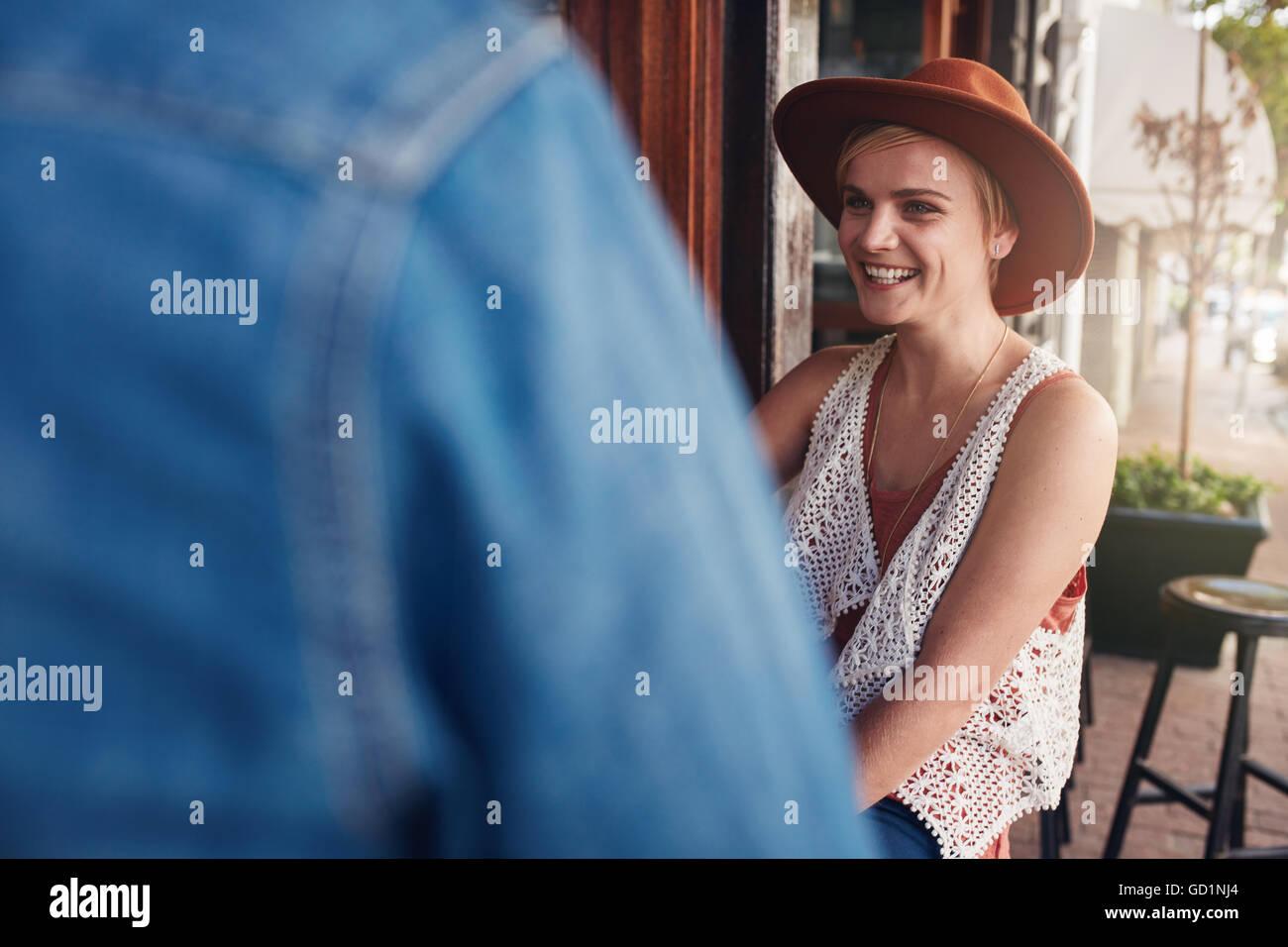 Sorridente giovane donna seduta a un coffee shop con il suo amico. I giovani seduti ad un tavolo del bar. Immagini Stock