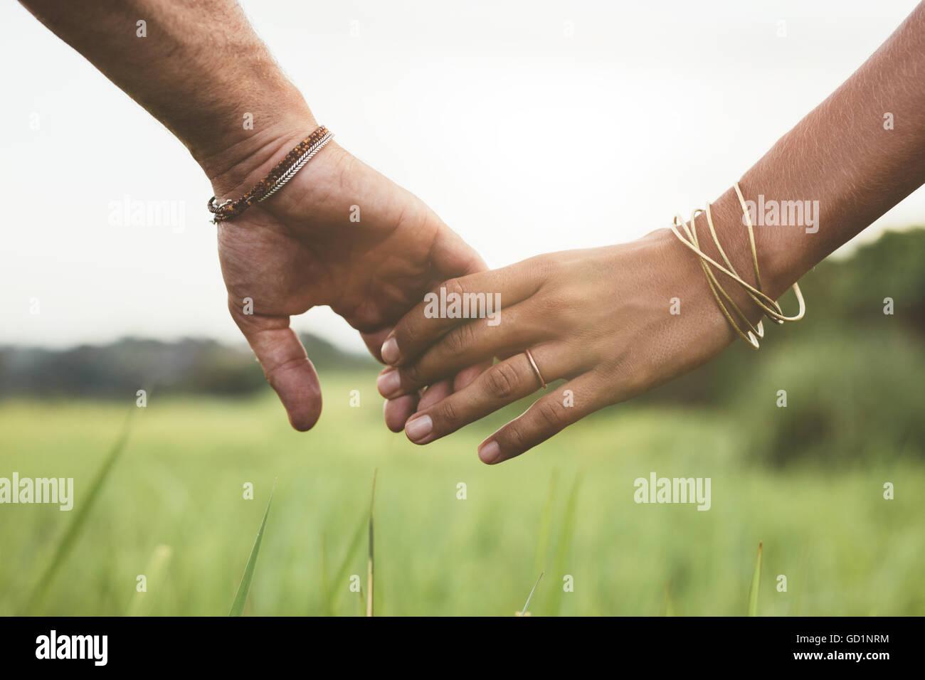 Inquadratura orizzontale di coppia giovane camminando attraverso il prato tenendo le mani con focus su mani . Immagini Stock