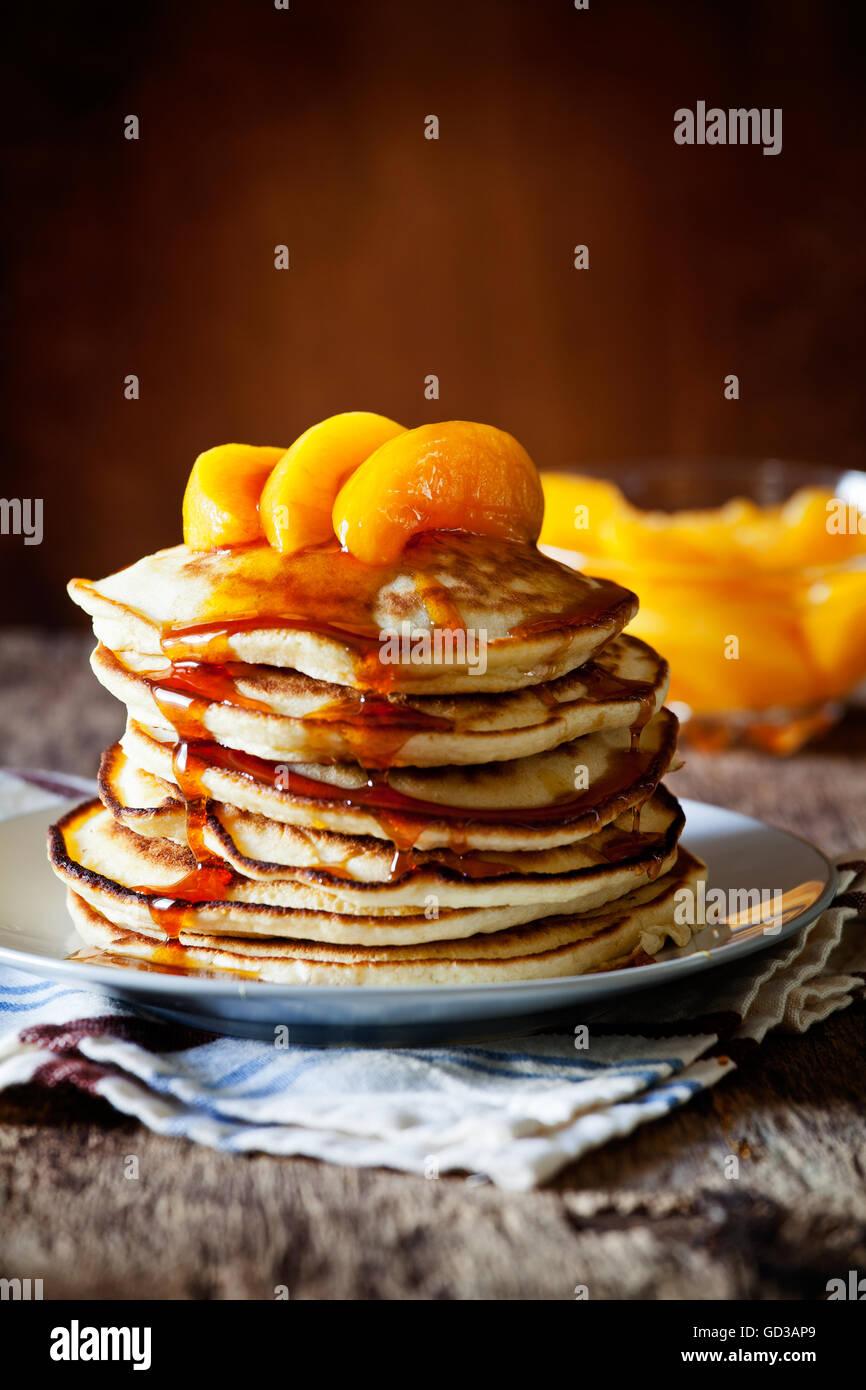 Pila di Pancake fatti in casa con purea di pesche Immagini Stock