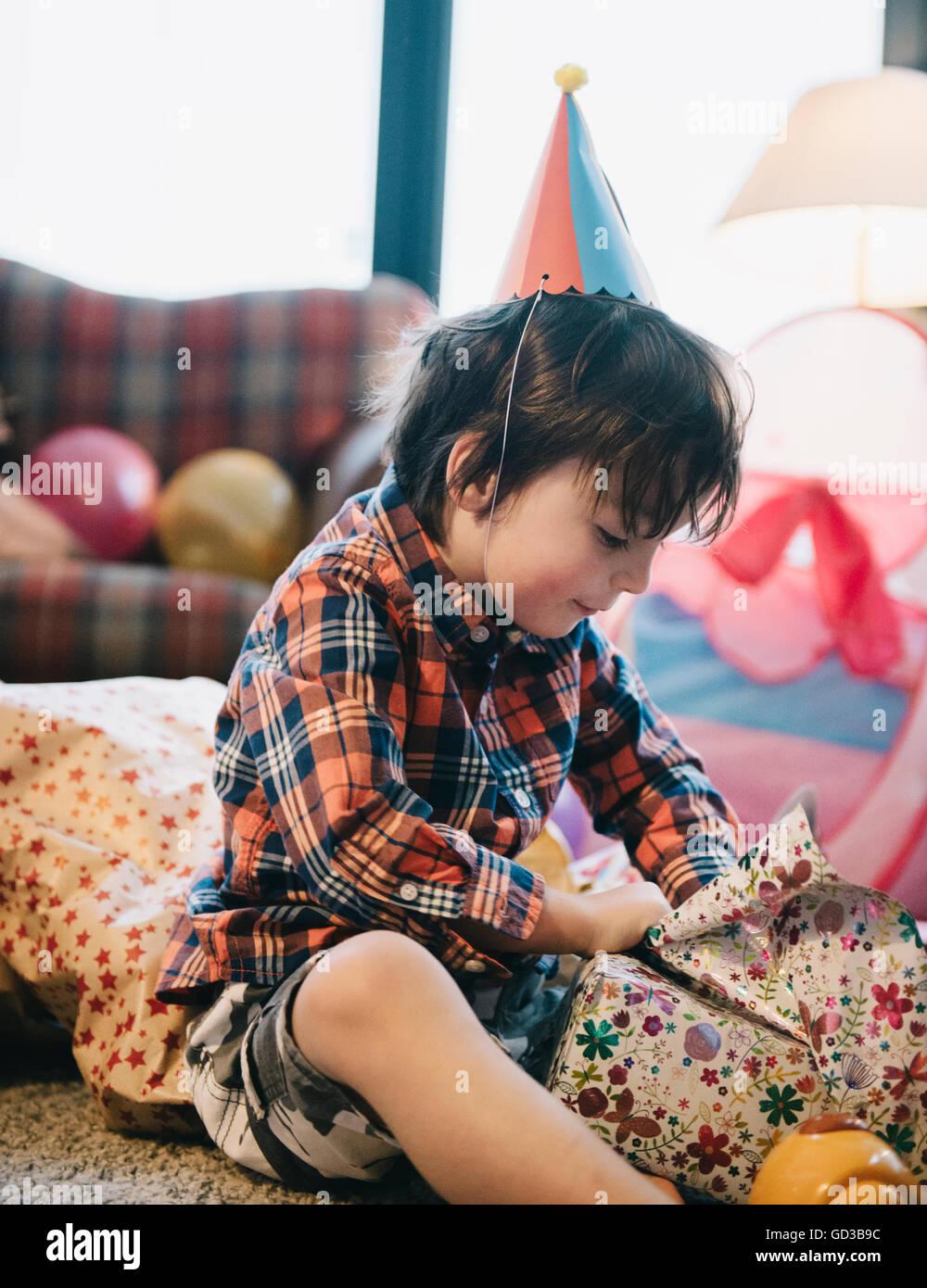 Un ragazzo svolgendo la sua presenta in corrispondenza della sua festa di compleanno. Immagini Stock