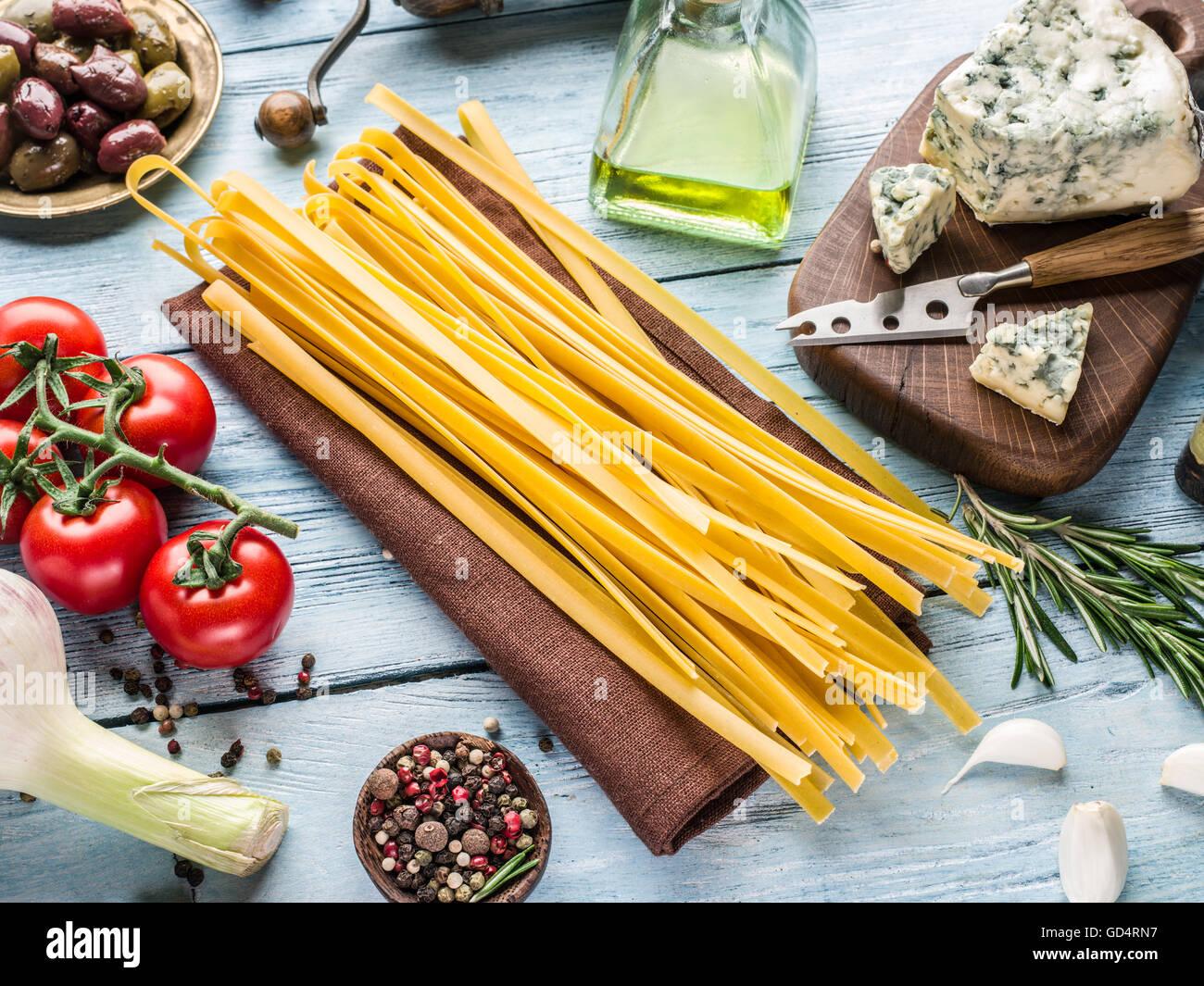 Ingredienti per la pasta. Cherry-pomodori, spaghetti, rosmarino e spezie sul tavolo di legno. Foto Stock